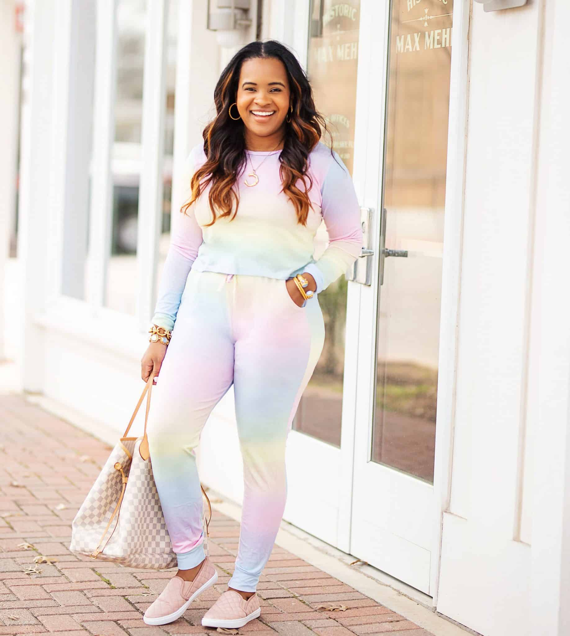 How to Grow Your Blog by popular Dallas lifestyle blog, Glamorous Versatility: image of a woman wearing a ombre sweatsuit pink sneakers, and holding a large bag.