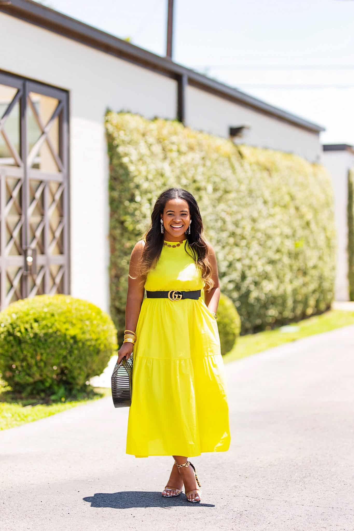 Day to night outfit for Summer styled by top US fashion blog, Glamorous Versatility: image of a woman wearing a Target yellow maxi dress, Gucci leather belt, Steve Madden sandals, Red Dress Boutique bamboo bag, and BaubleBar leopard earrings.
