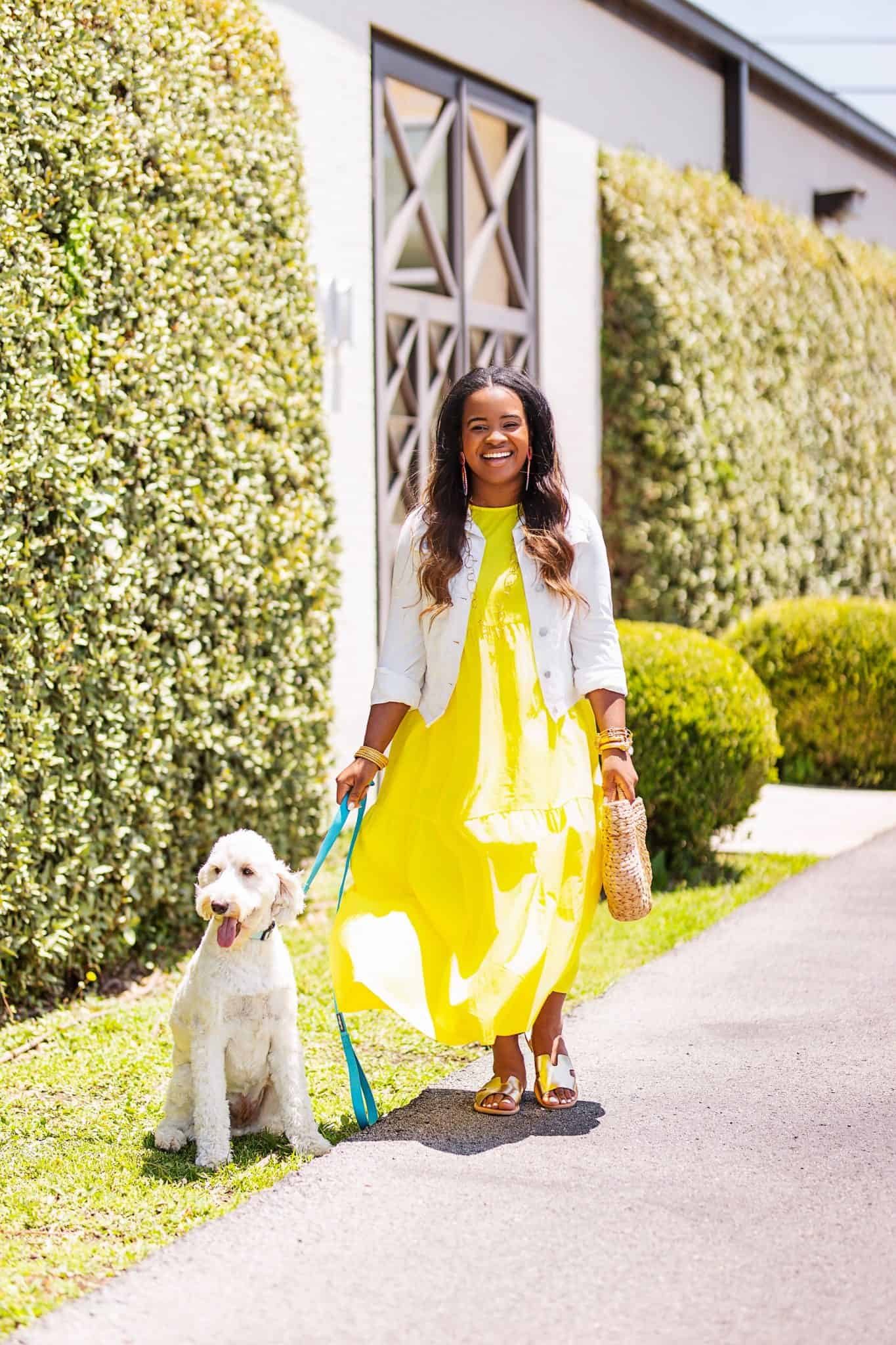 Day to night outfit for Summer styled by top US fashion blog, Glamorous Versatility: image of a woman wearing a Target yellow maxi dress, a Universal Thread white denim jacket, Red Dress Boutique gold sandals, Red Dress Boutique round rattan bag, and BaubleBar raffia earrings.