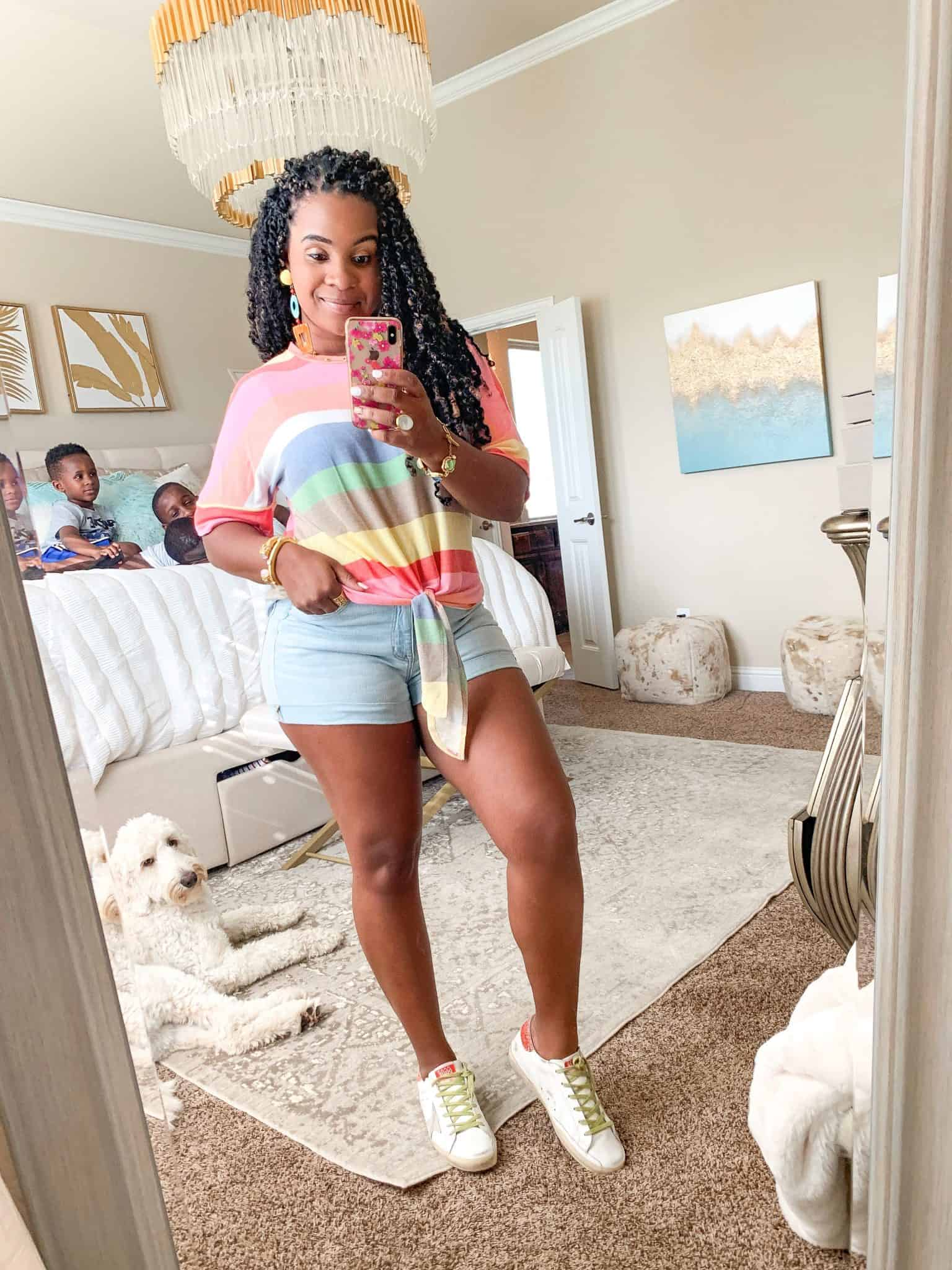 Pink Lily Boutique Favorites Under $50 featured by top US fashion blog, Glamorous Versatility: image of a woman wearing a Pink Lily rainbow striped top and denim shorts