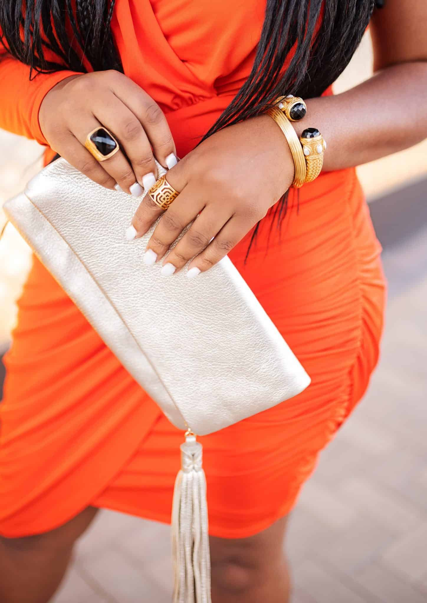 Summer Date Night Outfits featured by top US fashion blog, Glamorous Versatility: image of a woman wearing an orange Bebe dress and Steve Madden metallic sandals.