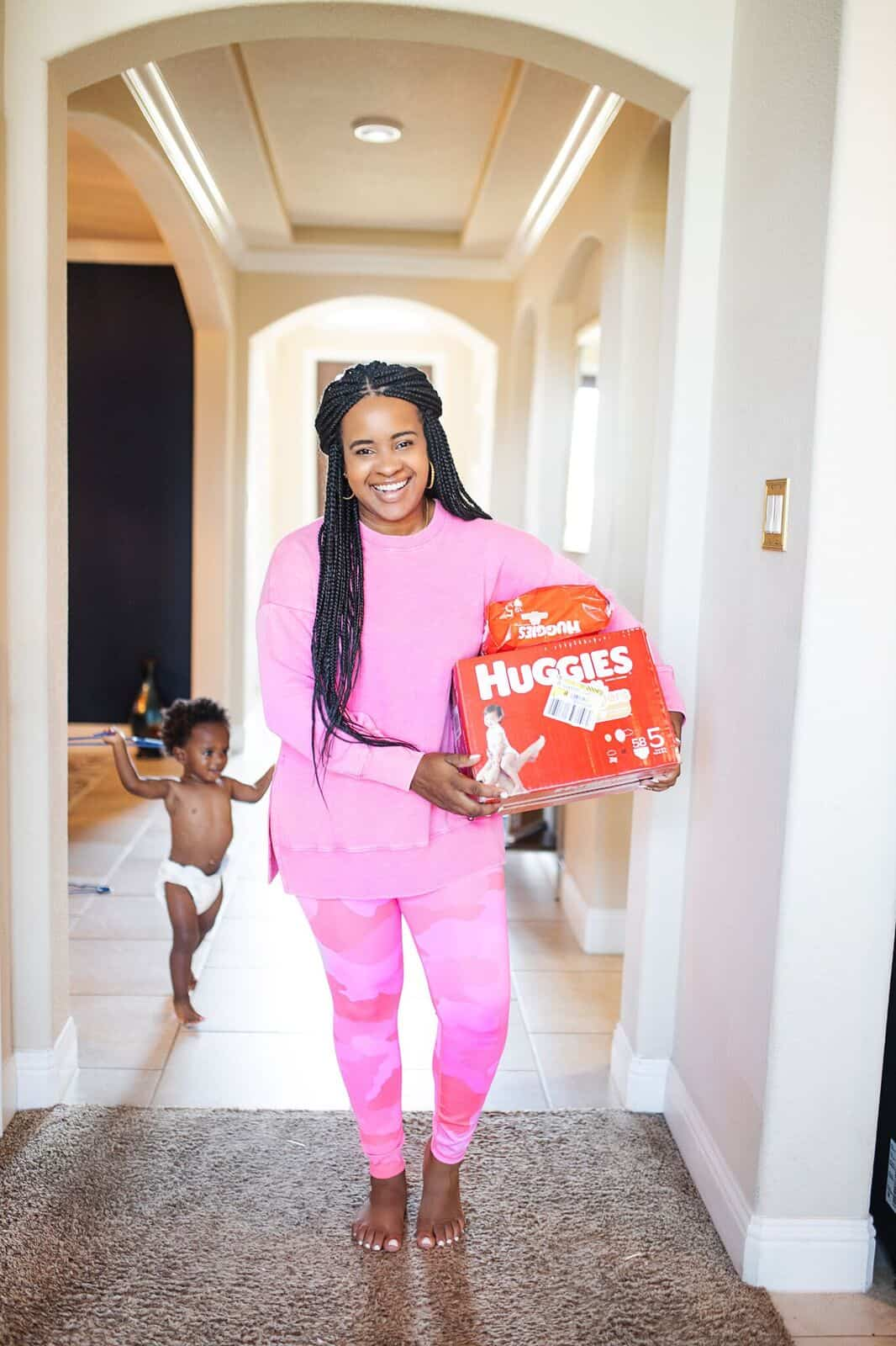 Basic Toddler Essentials by popular life and style blog, Glamorous Versatility: image of a woman holding a box of Huggies diapers.