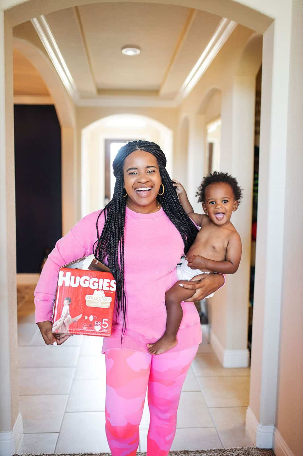 Basic Toddler Essentials by popular life and style blog, Glamorous Versatility: image of a woman holding a box of Huggies diapers and her baby.