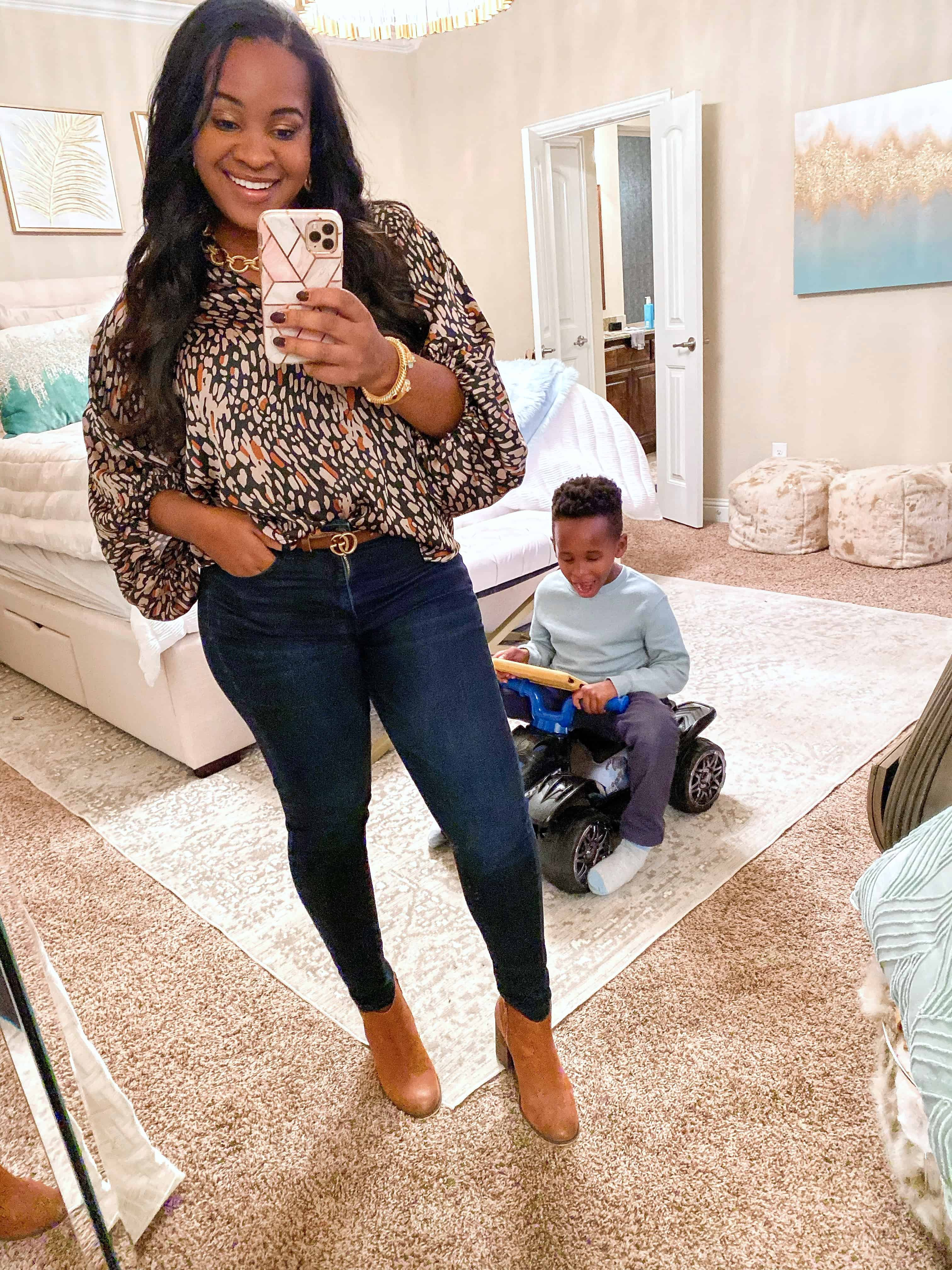 4 Cute Thanksgiving Outfit Ideas featured by top US fashion blog, Glamorous Versatility: image of a woman wearing a patterned blouse, skinny jeans and ankle booties