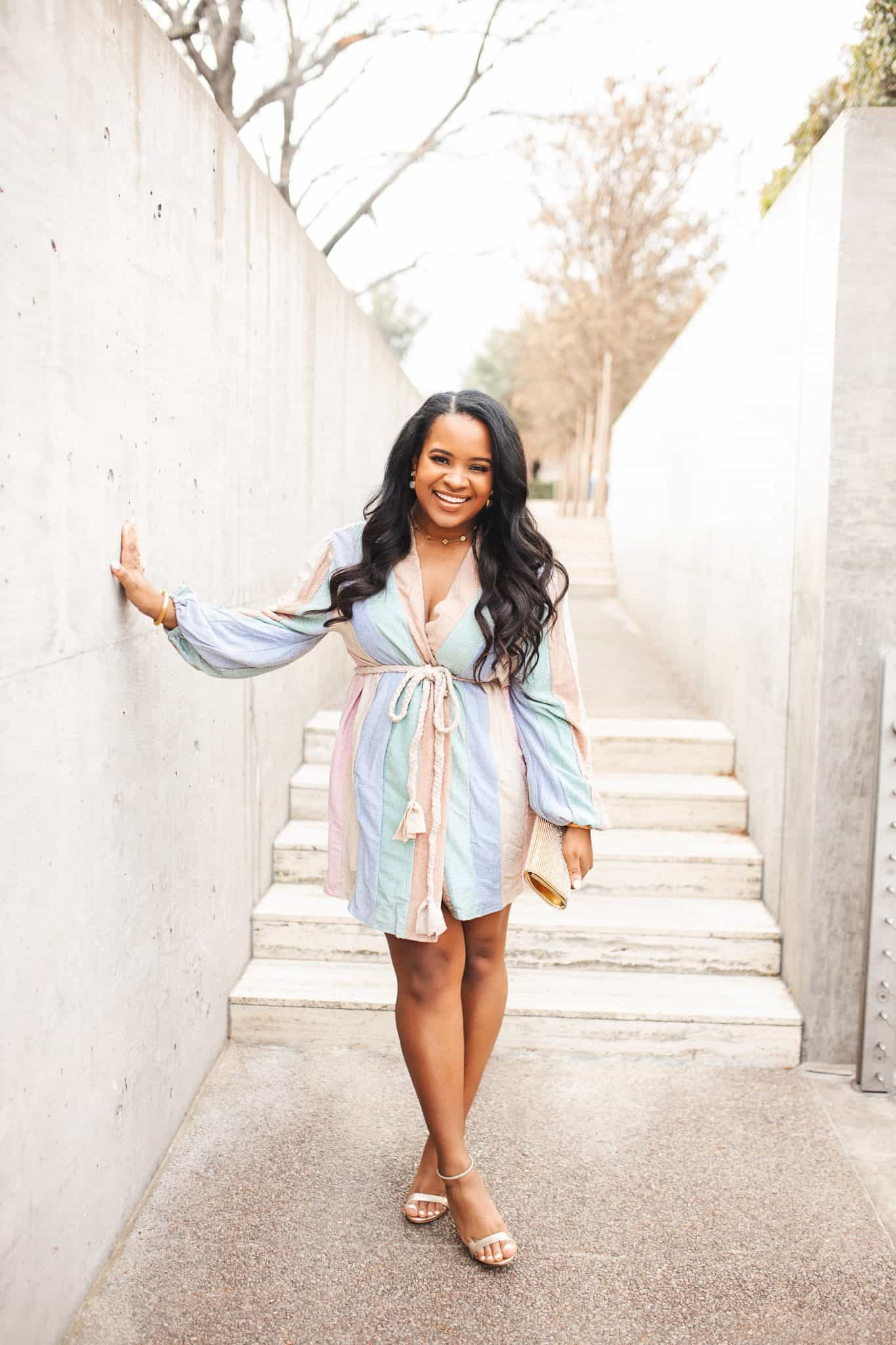 How to Prepare for a Successful New Year by popular Dallas life and style blog, Glamorous Versatility: image of a pregnant woman standing outside and wearing a pastel stripe romper.