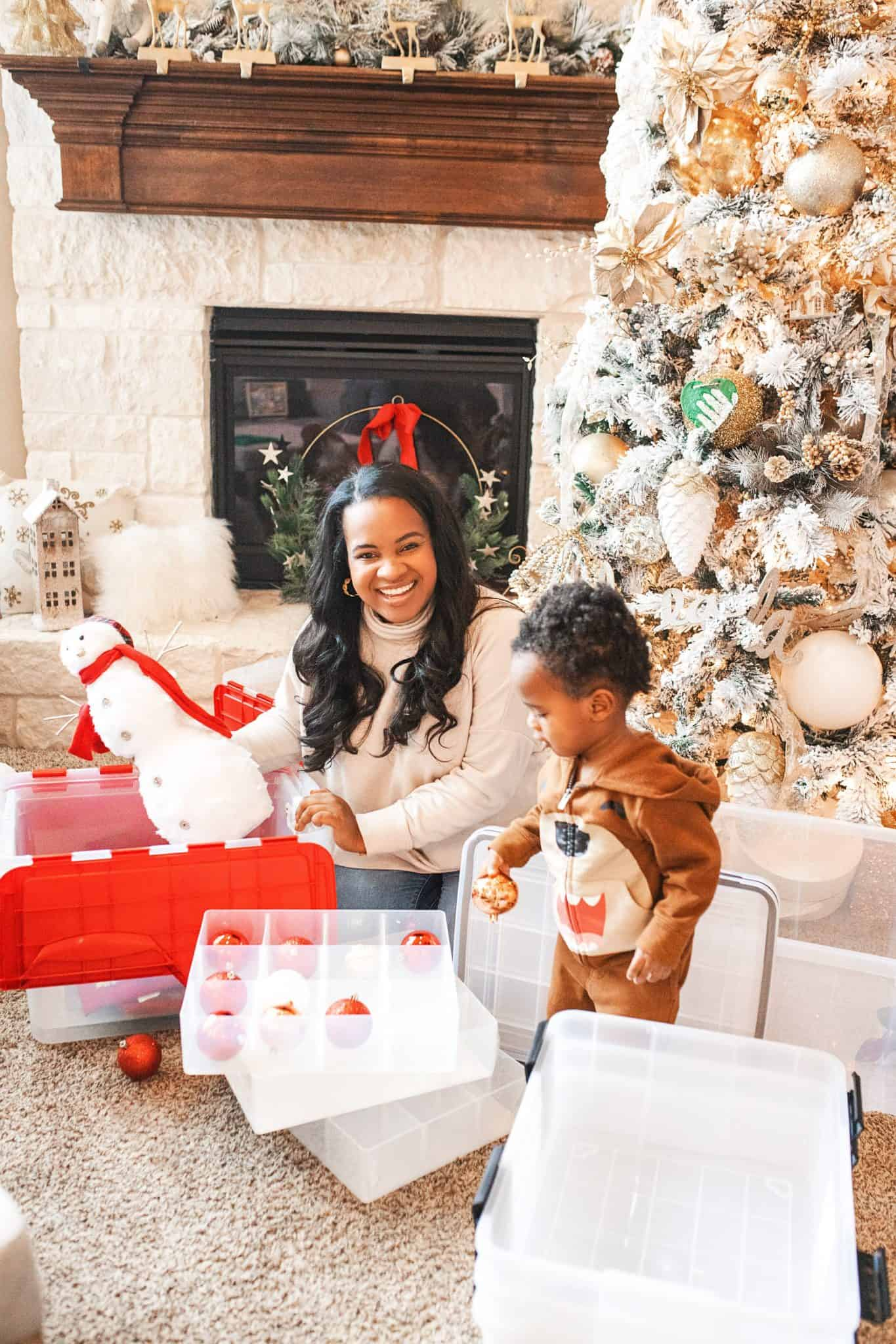 Top Home Organization Projects of 2019 by popular Dallas life and style blog, Glamorous Versatility: image of a woman and her son putting away Christmas decorations in storage bins.