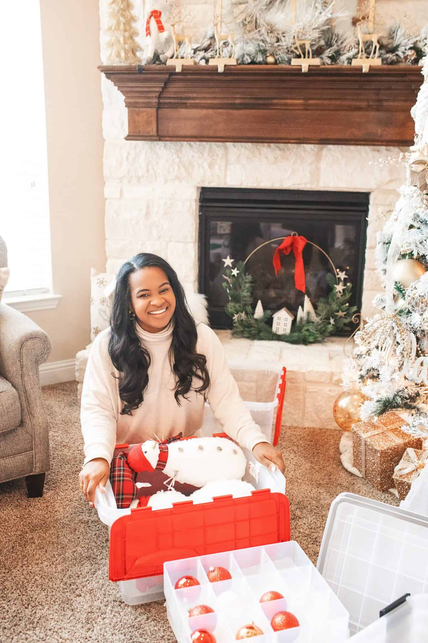 Top Home Organization Projects of 2019 by popular Dallas life and style blog, Glamorous Versatility: image of a woman putting her Christmas decorations in storage bins.