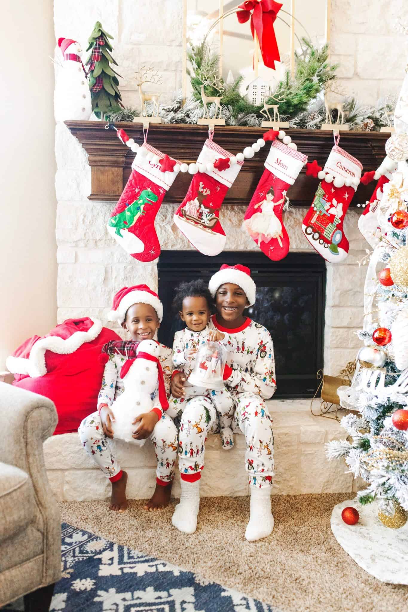 A Pottery Barn Kids Christmas by popular life and style blog, Glamorous Versatility: image of three boys wearing Pottery Barn Kids grinch pajamas and sitting in their living room that's decorated with Pottery Barn Brown Hair Fairy Quilted Stocking, Pottery Barn Kids Woodland Christmas Advent Calendar, Pottery Barn Kids Red Fleece Santa Bags, Pottery Barn Kids Frosted Pine Cone Garland, Pottery Barn Kids Light Up LED Glitter House Decor, Pottery Barn Kids Plaid Felt Wreath Decor, and Pottery Barn Kids Merry Christmas Glitter Garland.