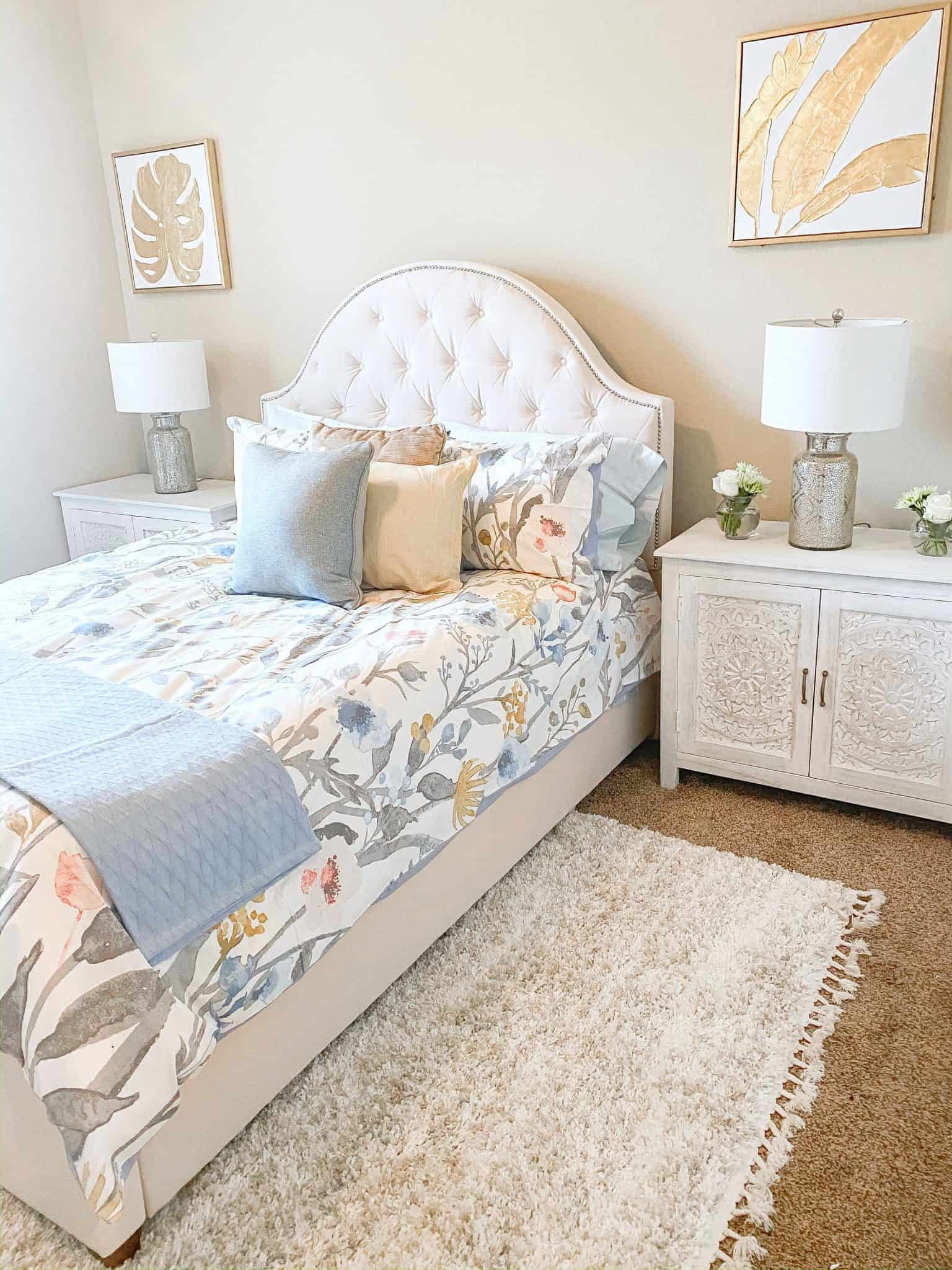 Guest Bedroom Decor Ideas by popular Dallas lifestyle blog, Glamorous Versatility: image of a guest bedroom decorated with a Home Depot Hover Image to Zoom Bradwick Ballet Beige Upholstered Queen Bed with Tufted Curved Back and Nailhead Detail, Home Depot Chennai White Wash Nightstand, Home Depot Chennai 3-Drawer White Wash Dresser, Home Depot Purcell 3-Piece Washed Denim Botanical Full/Queen Duvet Cover Set, Home Depot LaCrosse Medium Warmth White Queen Down Comforter, Home Depot Down Surround Jumbo Pillow, Home Depot Cotton Bamboo Misty Blue Woven Throw Blanket, Home Depot, 600 Thread Count Supima Cotton Sateen 4-Piece Queen Sheet Set in Raindrop, Home Depot Emilia 24.5 in. Mercury Silver Trellis Pattern Glass Table Lamp, and Home Depot Brooke Contemporary Ivory 8 ft. x 11 ft. Shag Area Rug.