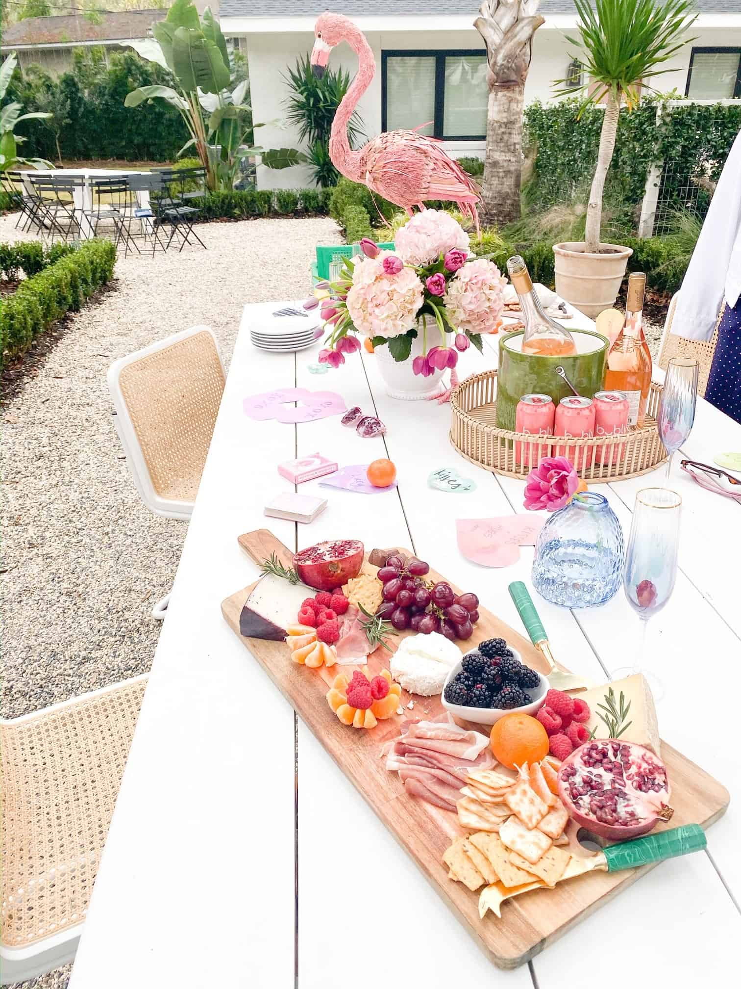 Behind The Scenes Draper James Trip by popular Dallas fashion blog, Glamorous Versatility: image of a white table set with a charcuterie board, Bubly drinks, pink floral arrangement and a pink flamingo decor at The Park on Saint Simons Island.
