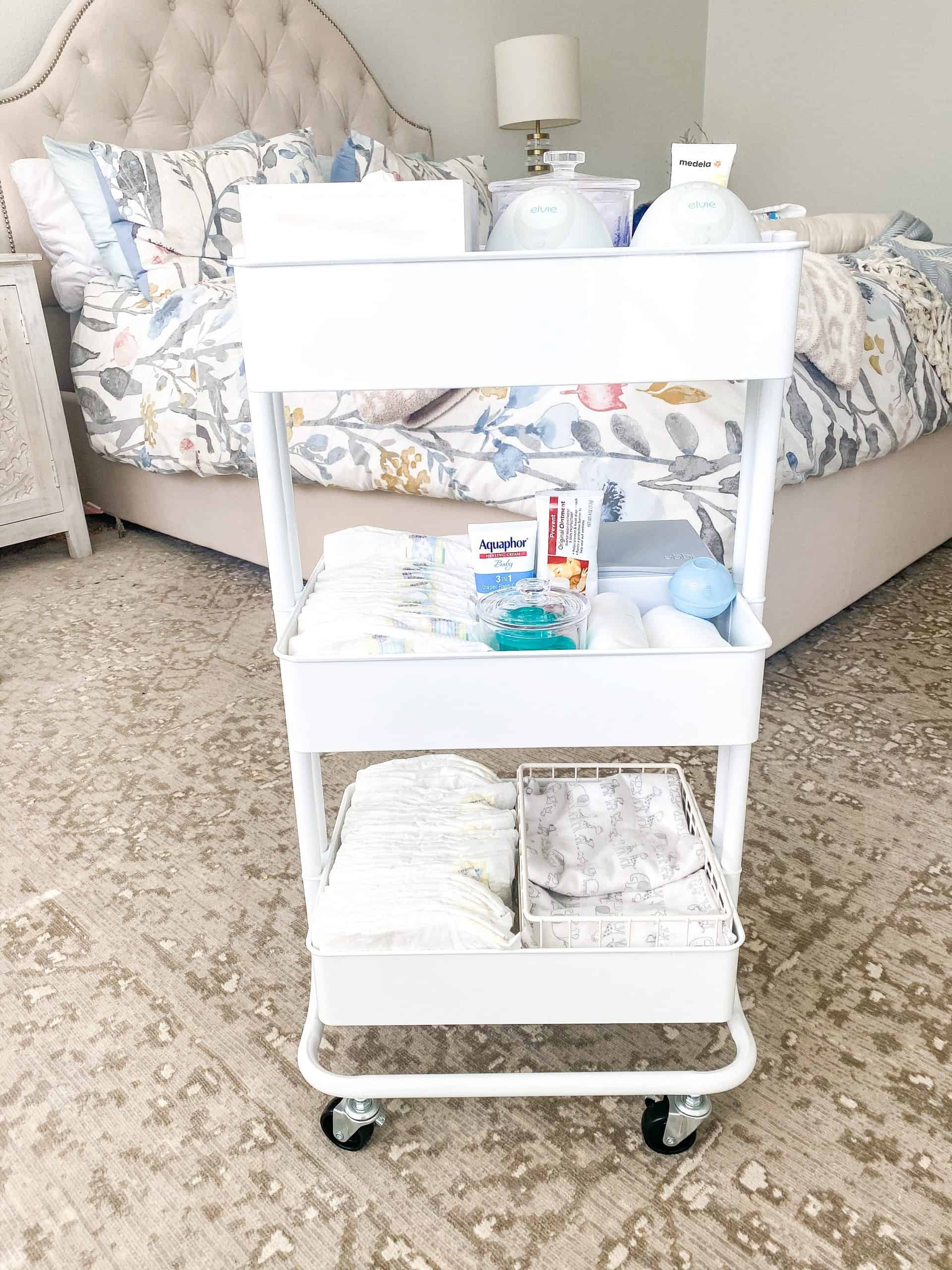 Newborn Cart by popular Dallas motherhood blog, Glamorous Versatility: image of a The Container Store White 3-Tier Rolling Cart, The Container Store White Stacking Wire Bins, Target Ubbi Wipes Dispenser, The Container Store Bliss Acrylic Canisters, The Container Store iDesign Linus Shallow Drawer Organizers, diapers, binkies, Aquaphor, and burp cloths.