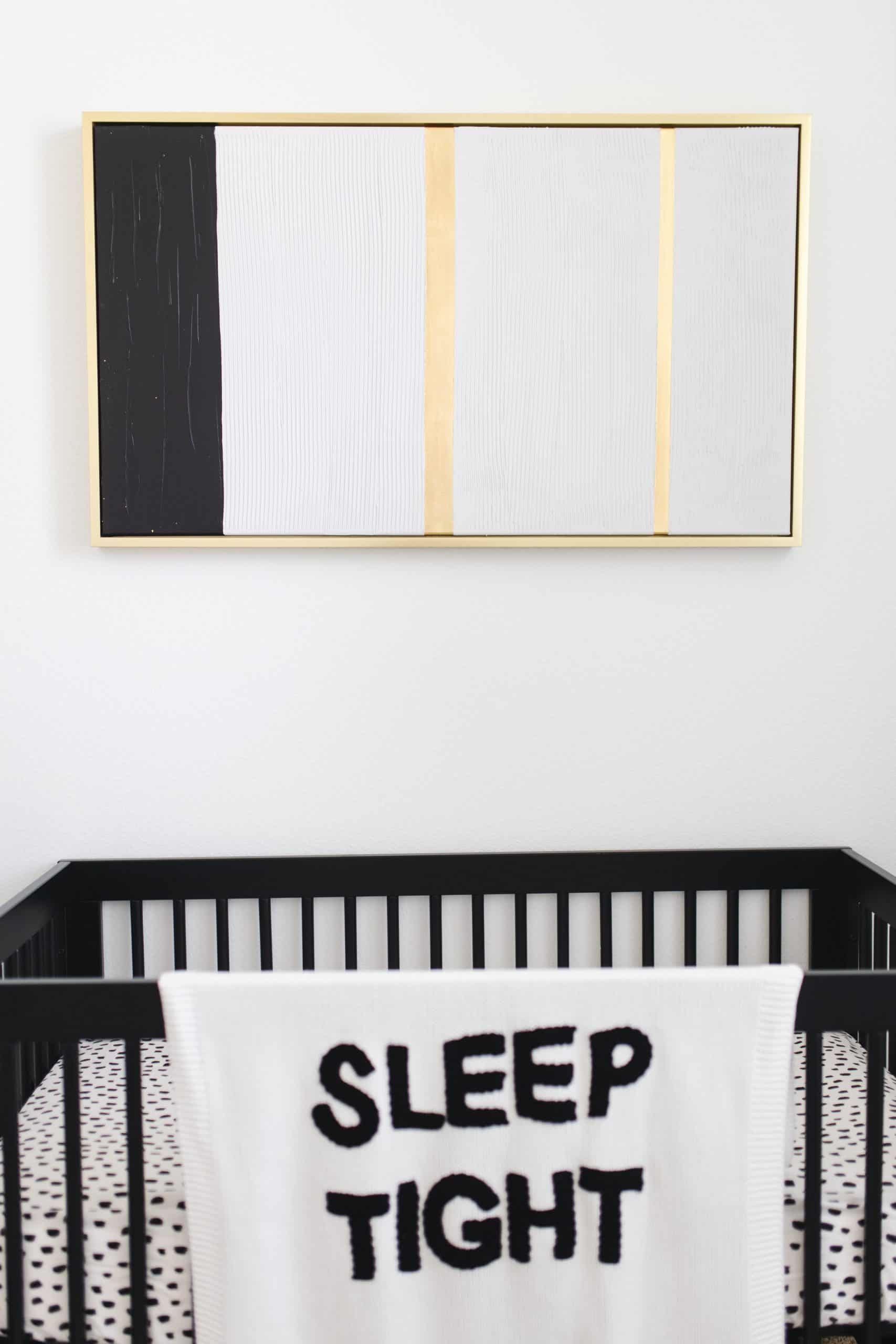 Pottery Barn Baby Registry by popular Dallas motherhood blog, Glamorous Versatility: image of black, white and gold painting hanging above a black crib with a Sleep Tight blanket hanging over the railing.