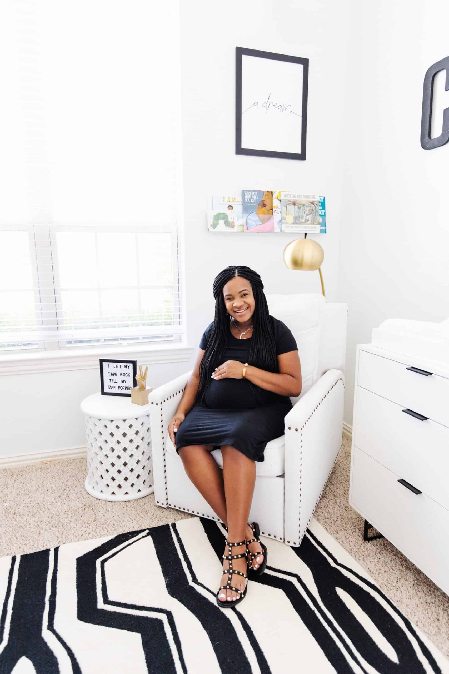 Baby Nursery by popular Dallas life and style blog, Glamorous Versatility: image of pregnant woman wearing a black maternity dress and and black studded sandals while sitting in a white glider chair in a baby nursery decorated with a Ellis Extra Wide Dresser And Topper Set, Knox Convertible Crib, Tyler Square Arm Swivel Glider & Recliner, west elm x pbk Mid-Century Narrow Tower Bookcase, Stella Side Table, Lullaby® Supreme Crib Mattress, Black and White Storage Collection (Large), Acrylic and Metallic Nursery Storage (Diaper Caddy & Table Storage), Metal Prism Storage, Acrylic Wall Shelf, Ubbi Diaper Pails, west elm x pbk Petite Arc Metal Floor Lamp, west elm x pbk Mid Century Puppy Plush Rocker, Coco Rug, Kingston Pendant, Finn + Emma® Mischief the Mouse Big Buddy & Rattle Buddy, Sleep Tight Baby Blanket, Lightning Pillow Arrow Sham, Black Brush Stroke Boppy® Nursing & Infant Support Pillow & Slipcover, Window Pane Muslin Swaddle Set, Chamois Broken Arrow Baby Blanket, Organic Black Brushstroke Dot Fitted Crib Sheet, west elm x pbk Organic Matelasse Changing Pad Cover, Modern Letters, Gilded Painted Art, Biggie Smalls Wall Trio, and Rapper's Delight Wall Art by Honeymoon. Hotel