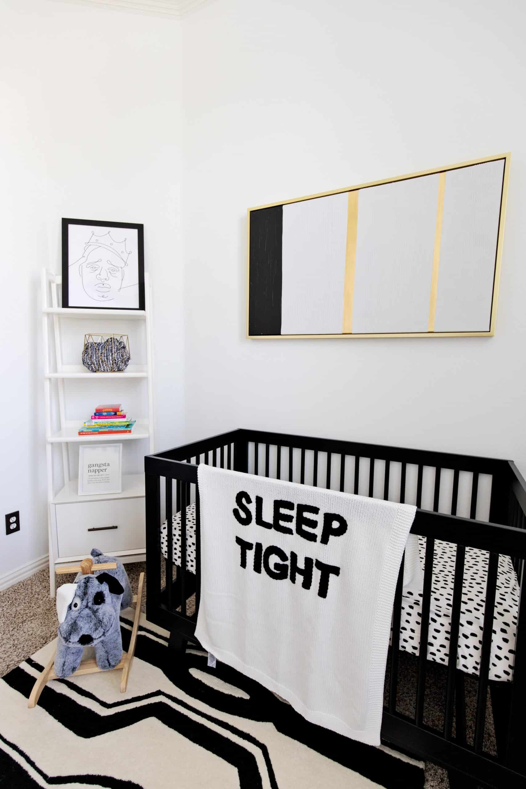 Baby Nursery by popular Dallas life and style blog, Glamorous Versatility: image of a baby nursery decorated with a Ellis Extra Wide Dresser And Topper Set, Knox Convertible Crib, Tyler Square Arm Swivel Glider & Recliner, west elm x pbk Mid-Century Narrow Tower Bookcase, Stella Side Table, Lullaby® Supreme Crib Mattress, Black and White Storage Collection (Large), Acrylic and Metallic Nursery Storage (Diaper Caddy & Table Storage), Metal Prism Storage, Acrylic Wall Shelf, Ubbi Diaper Pails, west elm x pbk Petite Arc Metal Floor Lamp, west elm x pbk Mid Century Puppy Plush Rocker, Coco Rug, Kingston Pendant, Finn + Emma® Mischief the Mouse Big Buddy & Rattle Buddy, Sleep Tight Baby Blanket, Lightning Pillow Arrow Sham, Black Brush Stroke Boppy® Nursing & Infant Support Pillow & Slipcover, Window Pane Muslin Swaddle Set, Chamois Broken Arrow Baby Blanket, Organic Black Brushstroke Dot Fitted Crib Sheet, west elm x pbk Organic Matelasse Changing Pad Cover, Modern Letters, Gilded Painted Art, Biggie Smalls Wall Trio, and Rapper's Delight Wall Art by Honeymoon. Hotel