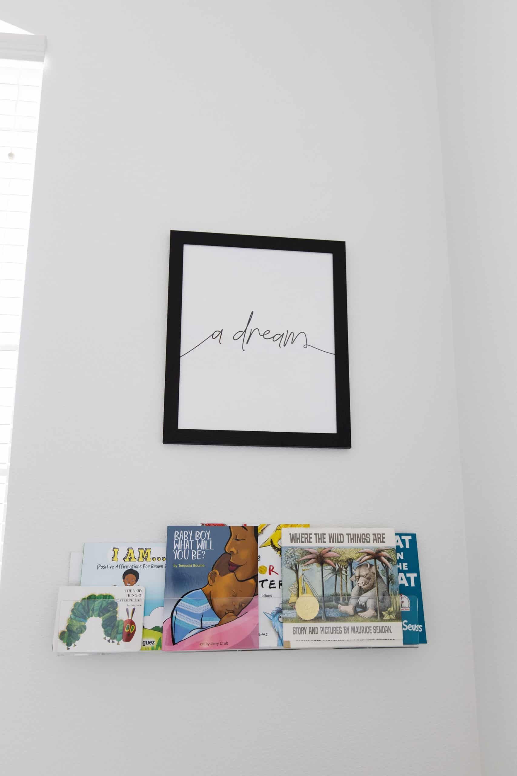 Baby Nursery by popular Dallas life and style blog, Glamorous Versatility: image of a baby nursery decorated with a Biggie Smalls Wall Trio, various picture books and acrylic wall mounted book shelf.