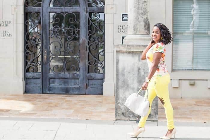How to Grow Your Blog by popular Dallas lifestyle blog, Glamorous Versatility: image of a woman wearing a multicolor shirt, distressed yellow jeans, nude heels and holding a white purse.