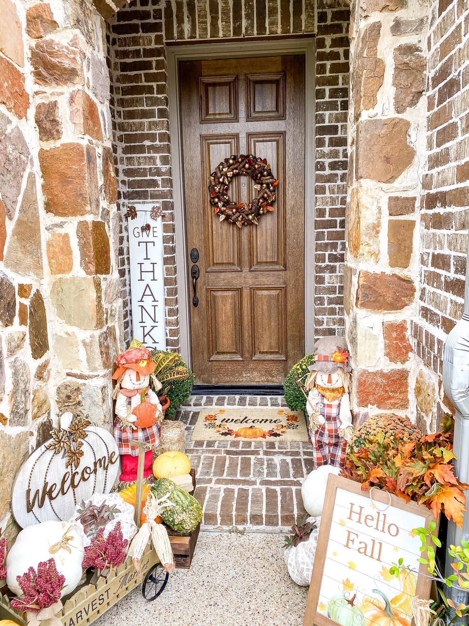 Fall Front Porch Ideas by popular Dallas life and style blog, Glamorous Versatility: image of two doodle breed dogs sitting on a front porch that decorated with a At Home scarecrow, At home Give Thanks sign, At Home pumpkin Welcome sign, At Home wagon, At home Styrofoam pumpkins, potted mums, At Home Hello Fall wooden sign, At Home Fall Welcome mat, and At Home fall wreath.