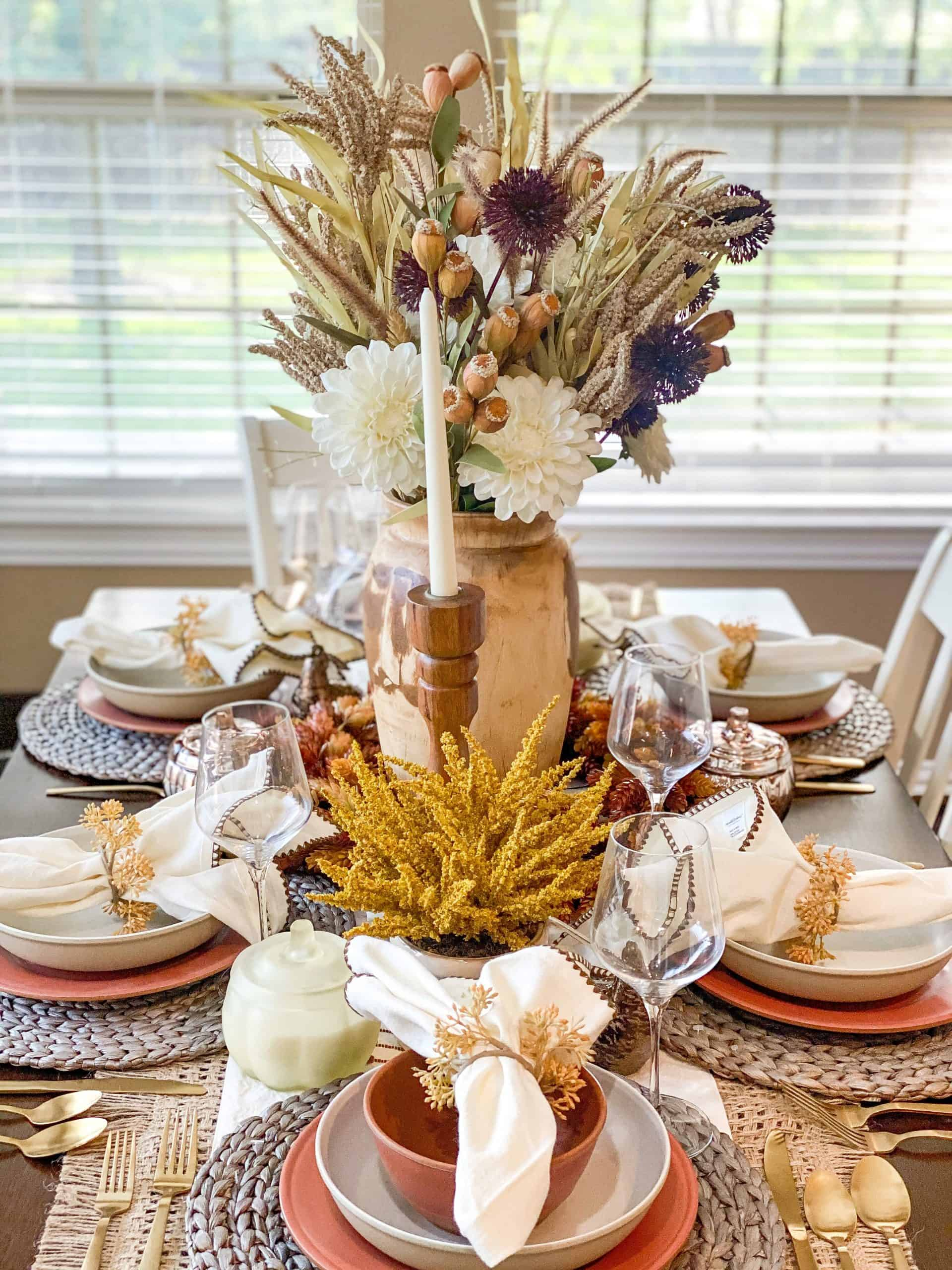 Fall Table Decor by popular Houston life and style blog, Glamorous Versatility: image of a dining table decorate with a Target table runner, straw place mats, linen napkins, wooden candle stick holders, white candle sticks, gold flatware, wooden vase, dried flowers, faux flowers, ceramic plates, ceramic bowls, and wine glasses.