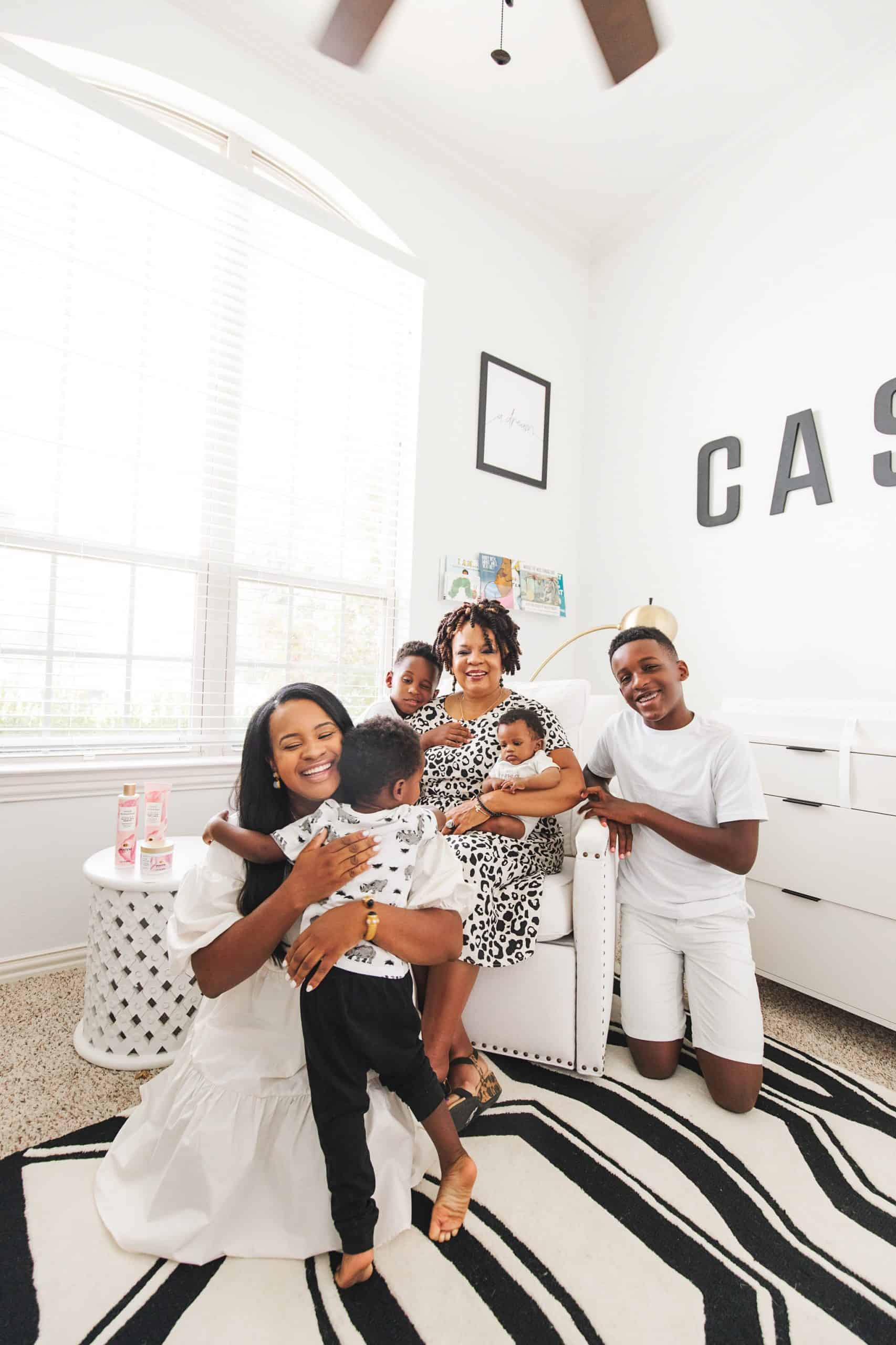 Self Confidence Tips by popular Dallas lifestyle blog, Glamorous Versatility: image of a woman her four sons and their grandma sitting in a nursery on a black and white rug and wearing black and white clothing.