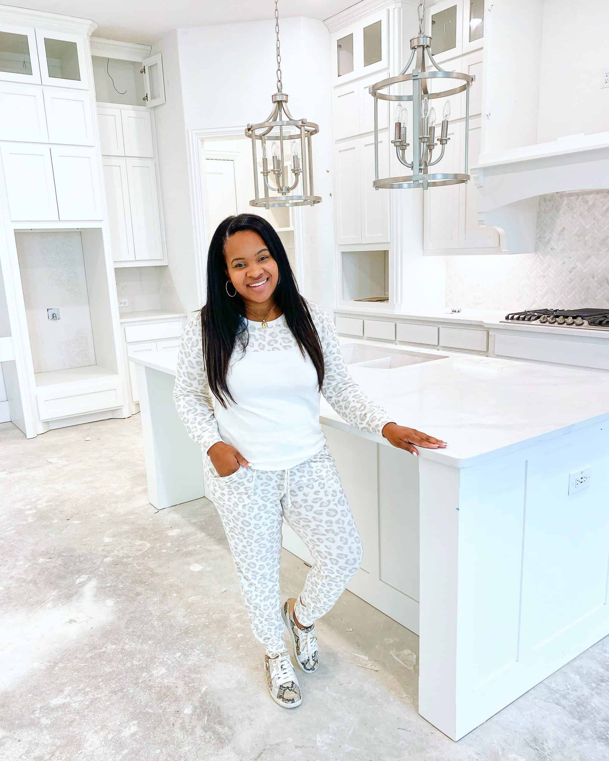 Best Nordstrom Fall Loungewear featured by top Dallas fashion blogger, Glamorous Versatility | Comfortable Loungewear by popular Dallas fashion blog, Glamorous Versatility: image of a woman standing in an unfinished kitchen and wearing a leopard print loungewear set with some snakeskin sneakers.