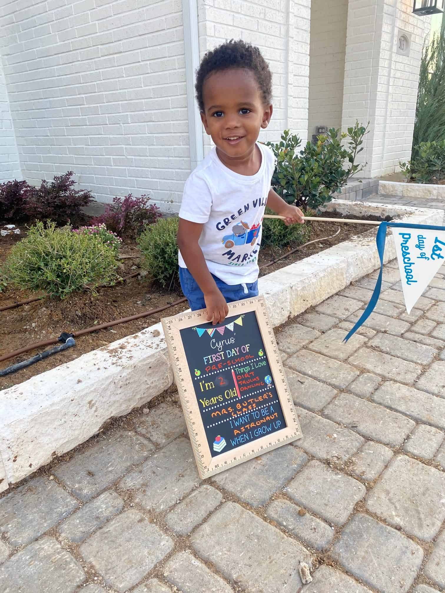Etsy Favorites by popular Dallas life and style blog, Glamorous Versatility: image of a little boy holding a first day of school board and first day of preschool pennant flag.