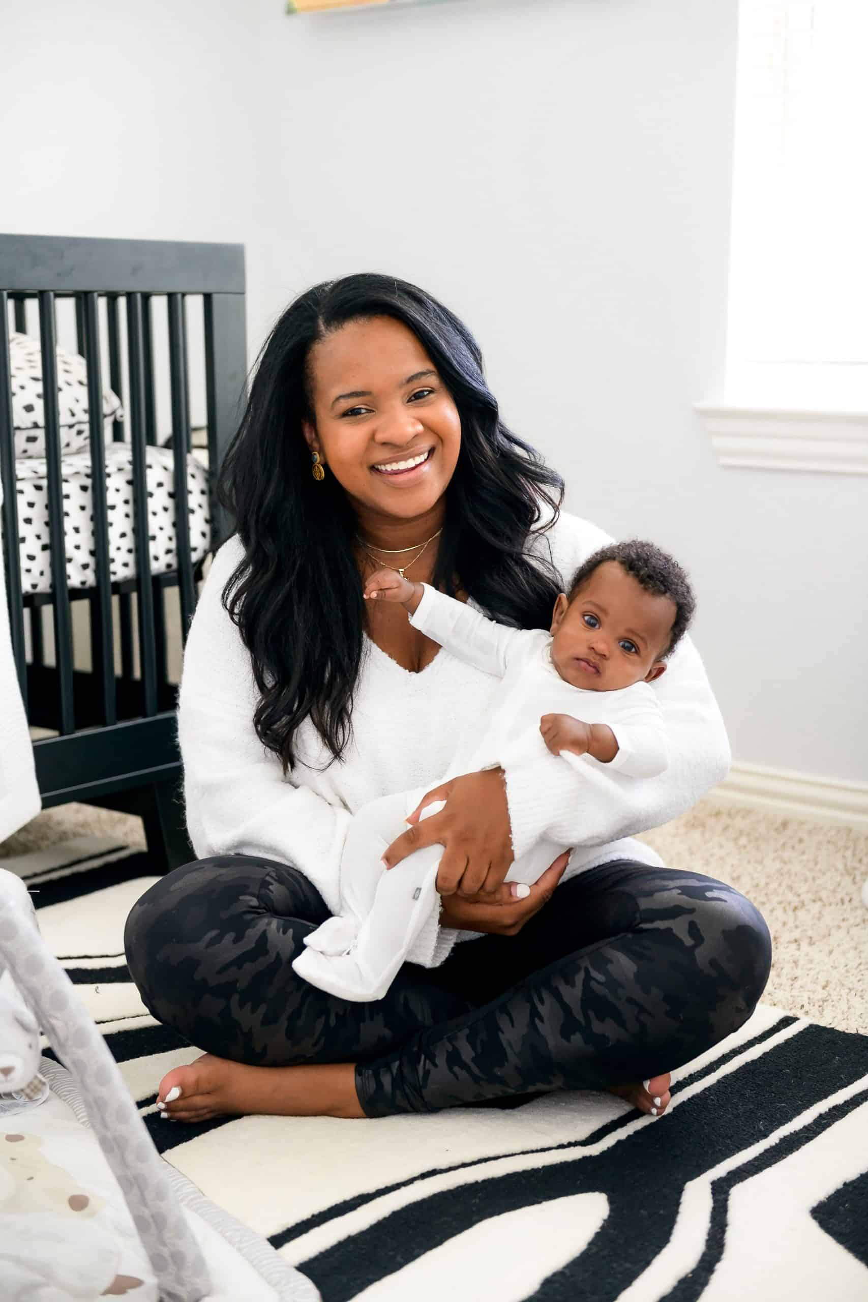 Pottery Barn Baby Registry by popular Dallas motherhood blog, Glamorous Versatility: image of a mom wearing a Judith March STELLA SWEATER and Spanx Faux Leather Camo Leggings and sitting on a black and white rug in her baby's nursery room and holding her baby in her lap.