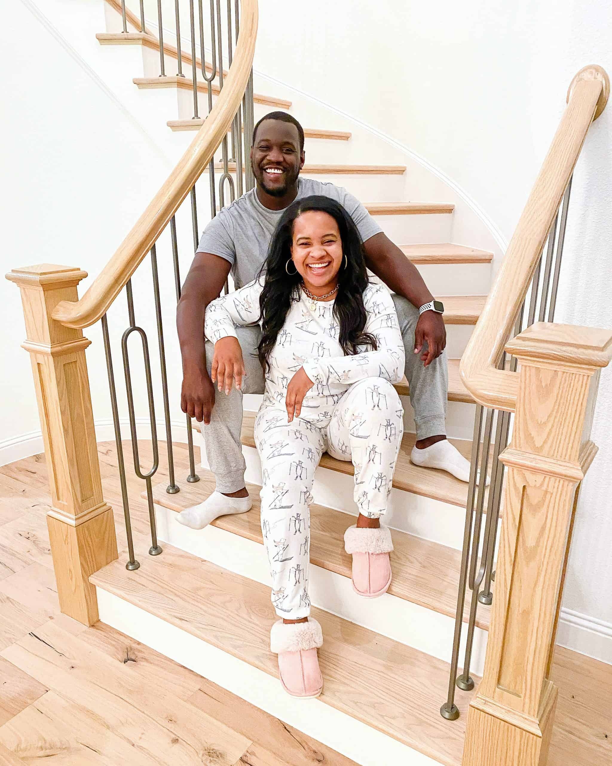 Cozy Gifts by popular Dallas life and style blog, Glamorous Versatility: image of a woman wearing a Nordstrom BP. Print Comfy Pajamas set with a pair of pink UGG slippers and sitting on the stairs in front of her husband who is wearing a grey pajama set.