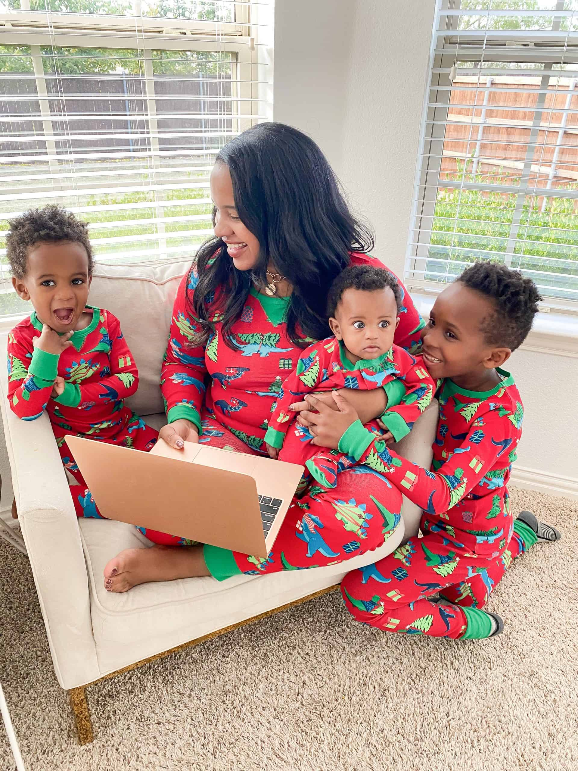 Giving Back by popular Dallas lifestyle blog, Glamorous Versatility: image of a mom and her 3 sons wearing matching Christmas pajamas and sitting on a white chair while looking at a laptop.