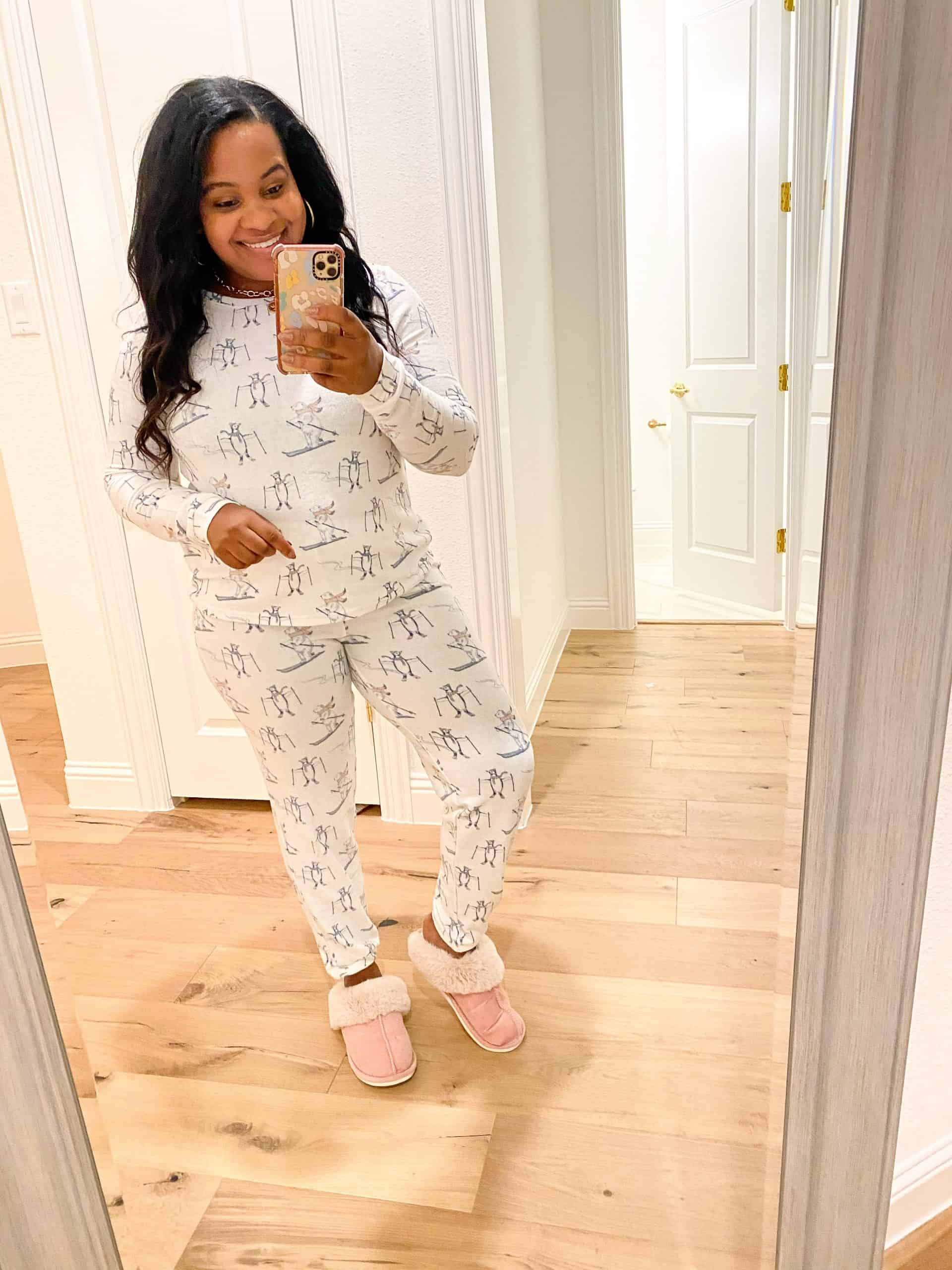Cozy Gifts by popular Dallas life and style blog, Glamorous Versatility: image of a woman wearing a Nordstrom BP. Print Comfy Pajamas set with a pair of pink UGG slippers.