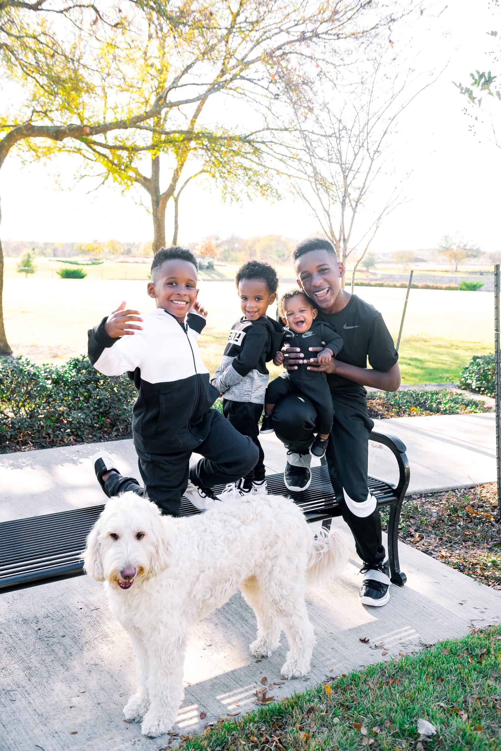 Nike Holiday by popular Dallas fashion blog, Glamorous Versatility: image of four brothers wearing Nike gear and sitting outside on a park bench with their dog.