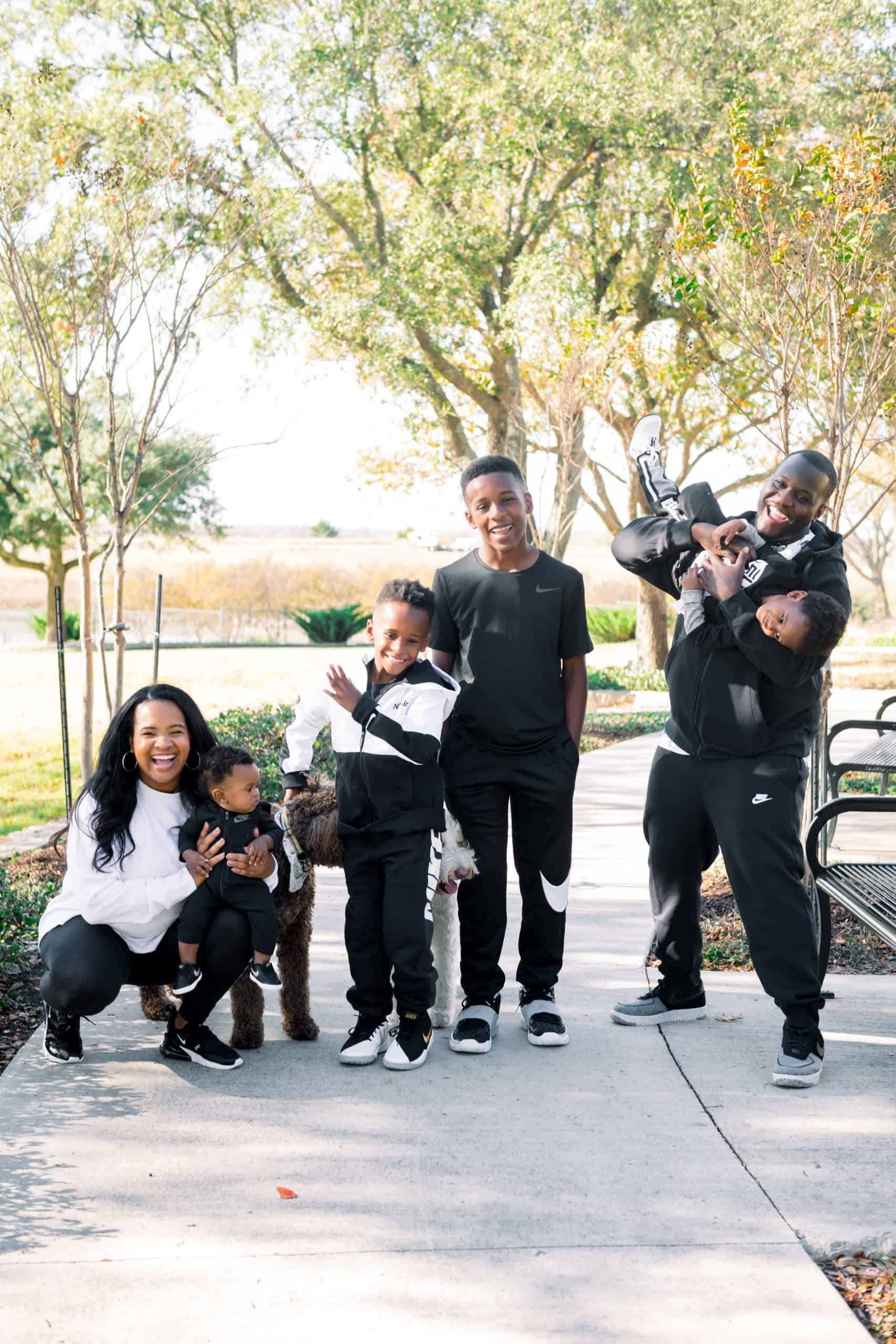 Nike Holiday by popular Dallas fashion blog, Glamorous Versatility: image of family wearing Nike gear and sitting outside at a park with their two dogs.