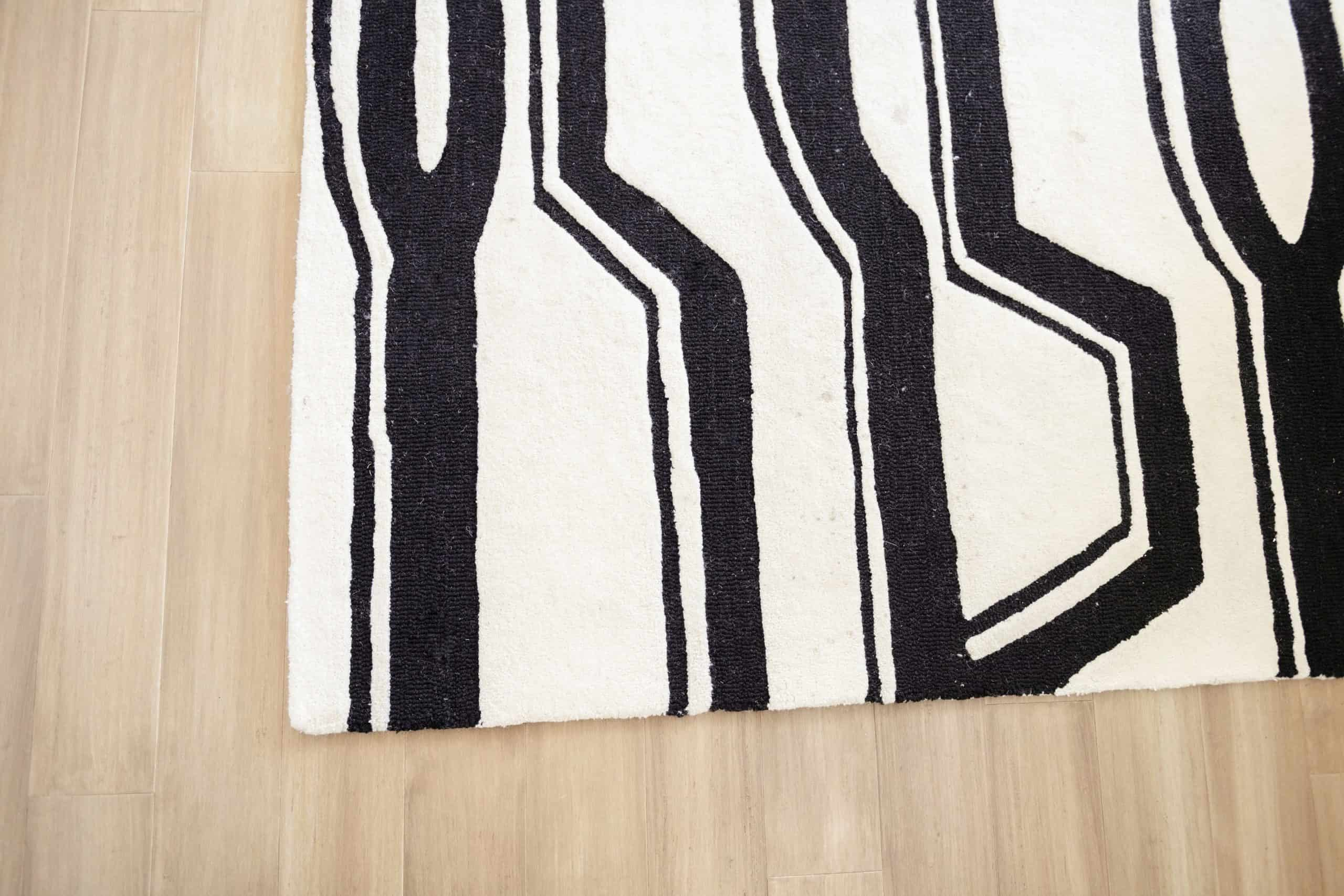 Wood Floor Installation by popular Dallas life and style blog, Glamorous Versatility: image of a black and white rug on a light wood floor.