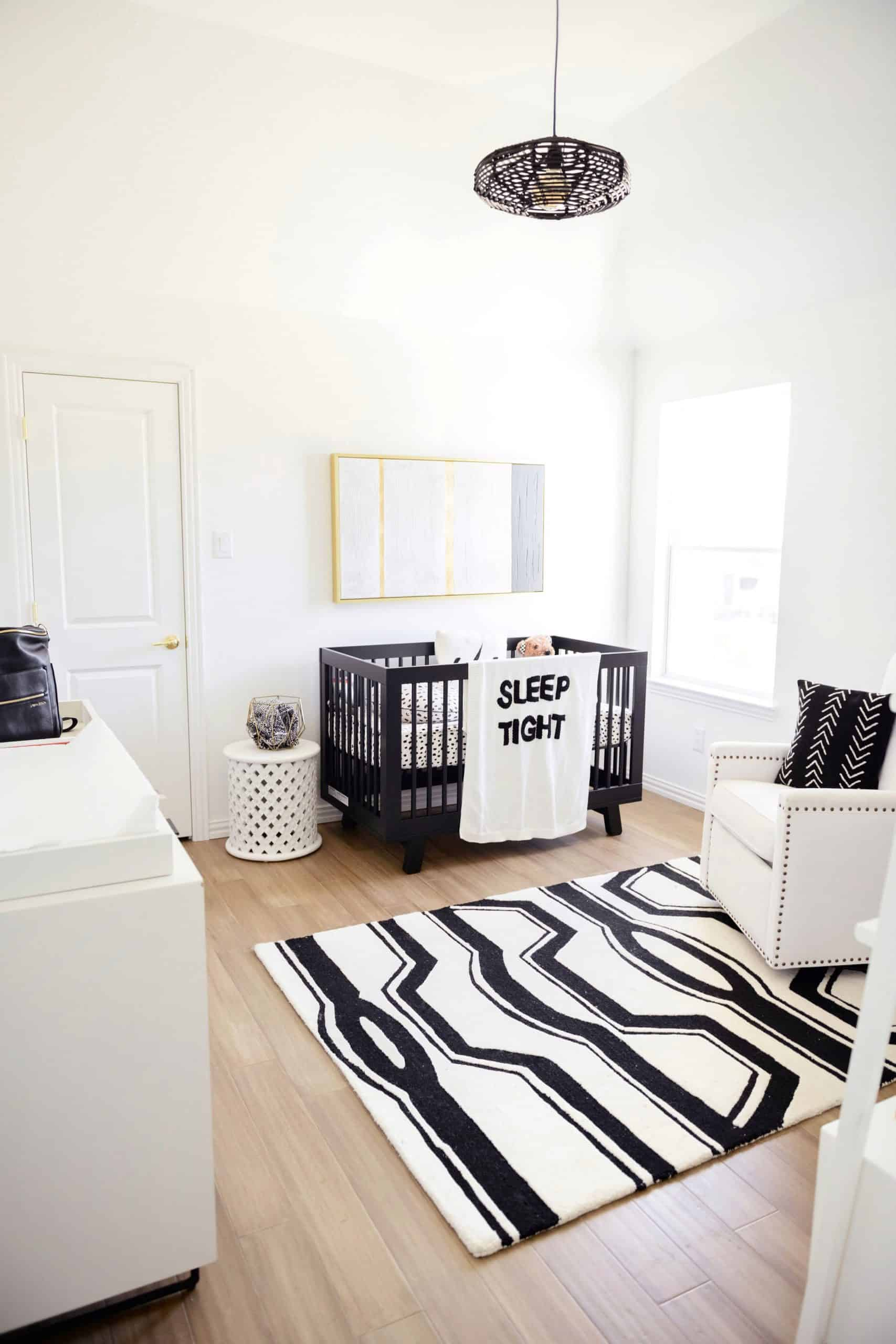 Wood Floor Installation by popular Dallas life and style blog, Glamorous Versatility: image of a boys room with light wood floors, black light fixture, black crib, black and white rug, white dresser, and white glider chair.