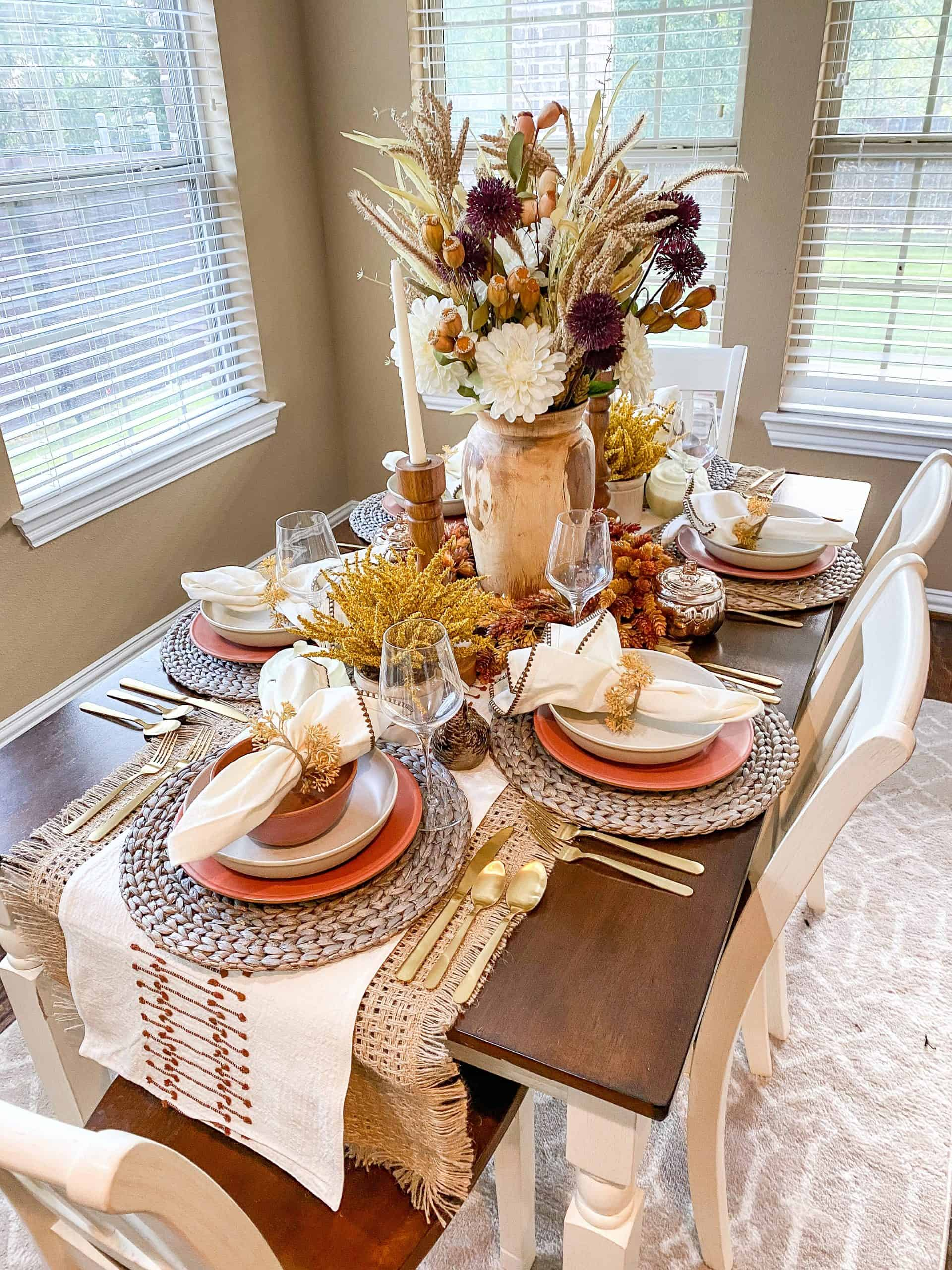Thanksgiving Prep by popular Dallas lifestyle blog, Glamorous Versatility: image of table set with straw placemats, white fabric table runner, gold utensils, a wooden vase filled with dried flowers, clear wine glasses, white ceramic plates, terra cotta bowls, orange ceramic plates, wooden candlestick holders, white candlesticks, and white fabric napkins.