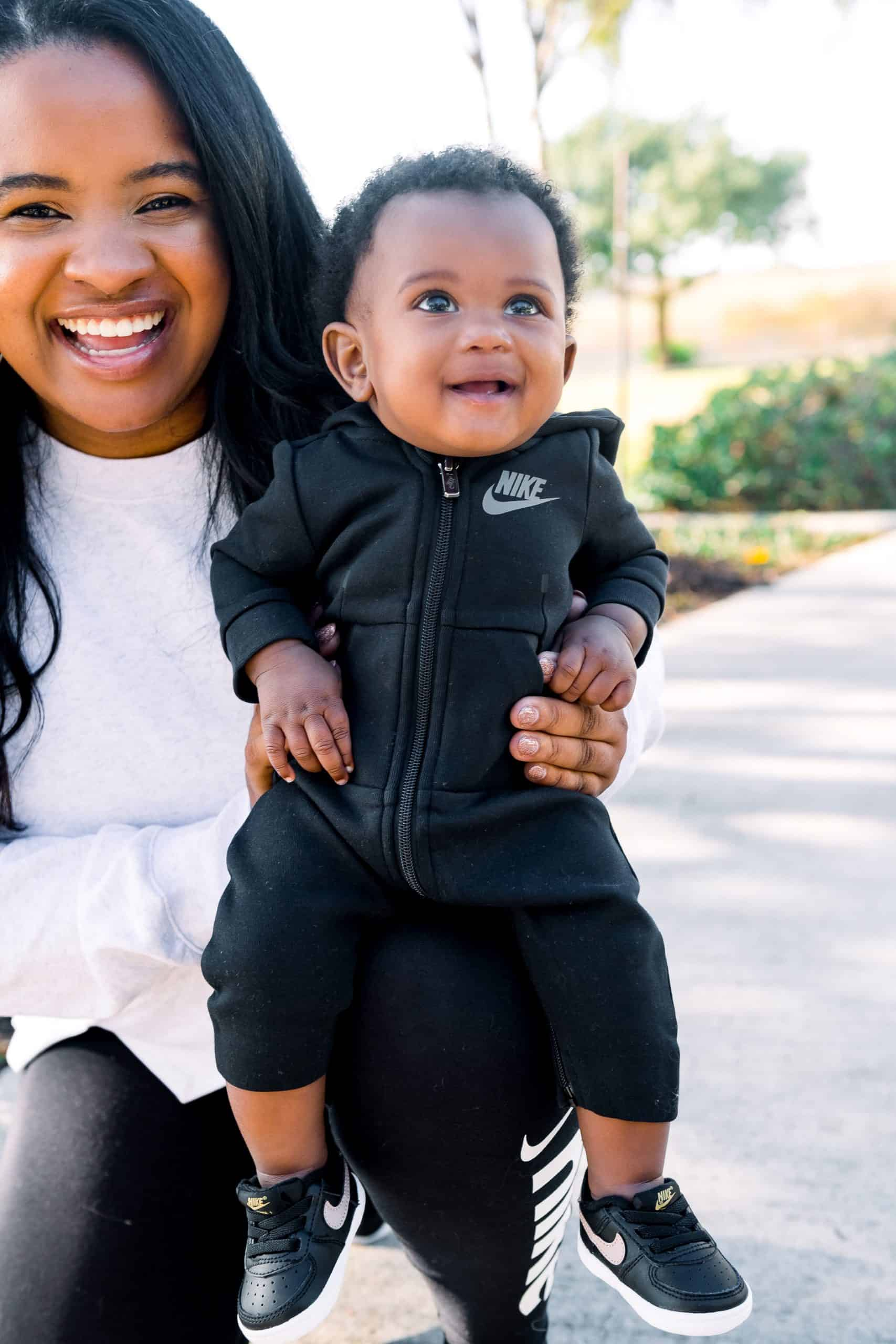 Nike Holiday by popular Dallas fashion blog, Glamorous Versatility: image of a mom and her baby wearing Nike attire and sitting together outside.