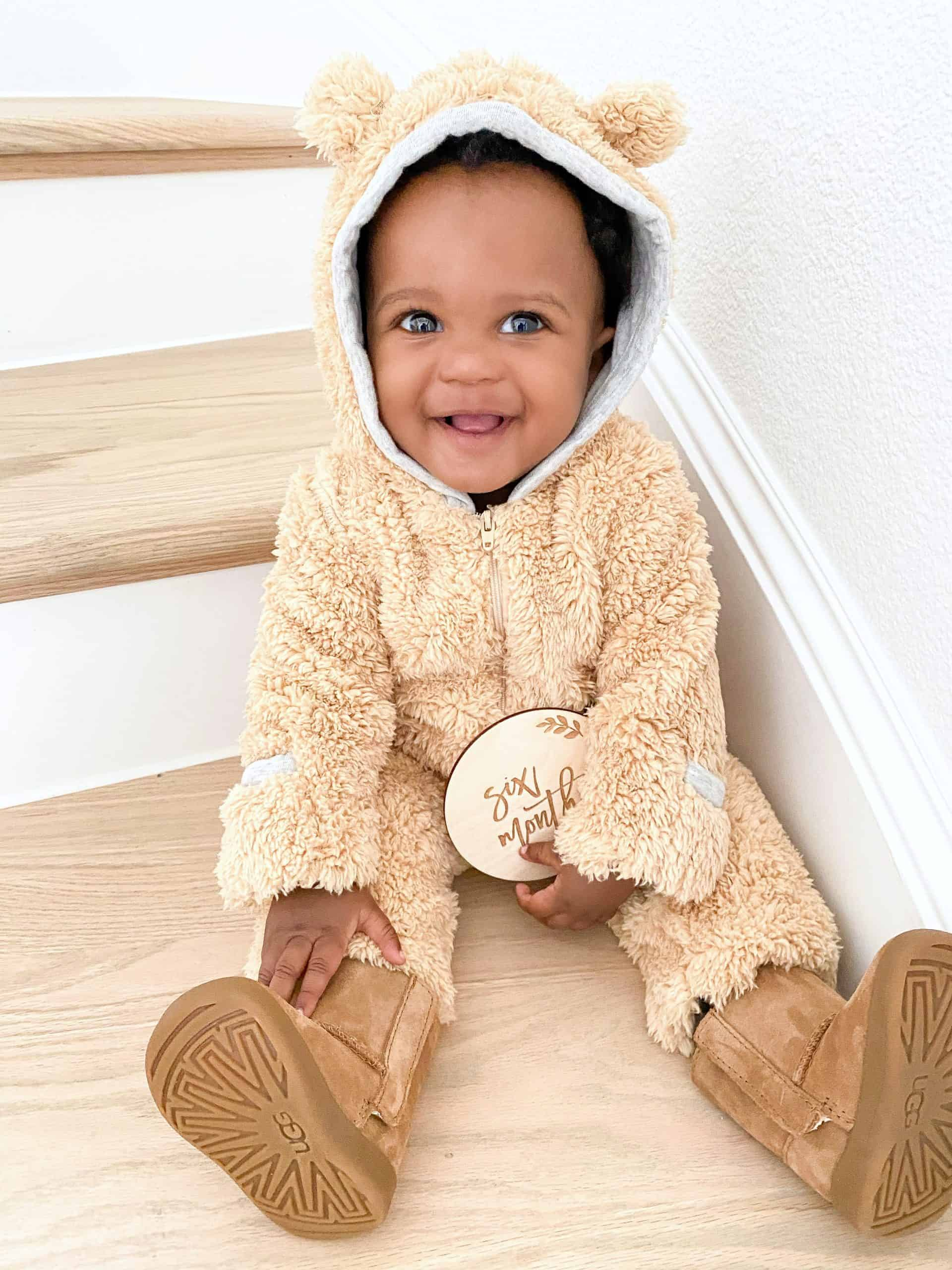 Birth Story by popular Dallas motherhood blog, Glamorous Versatility: image of a baby wearing a bear suite and baby Uggs.