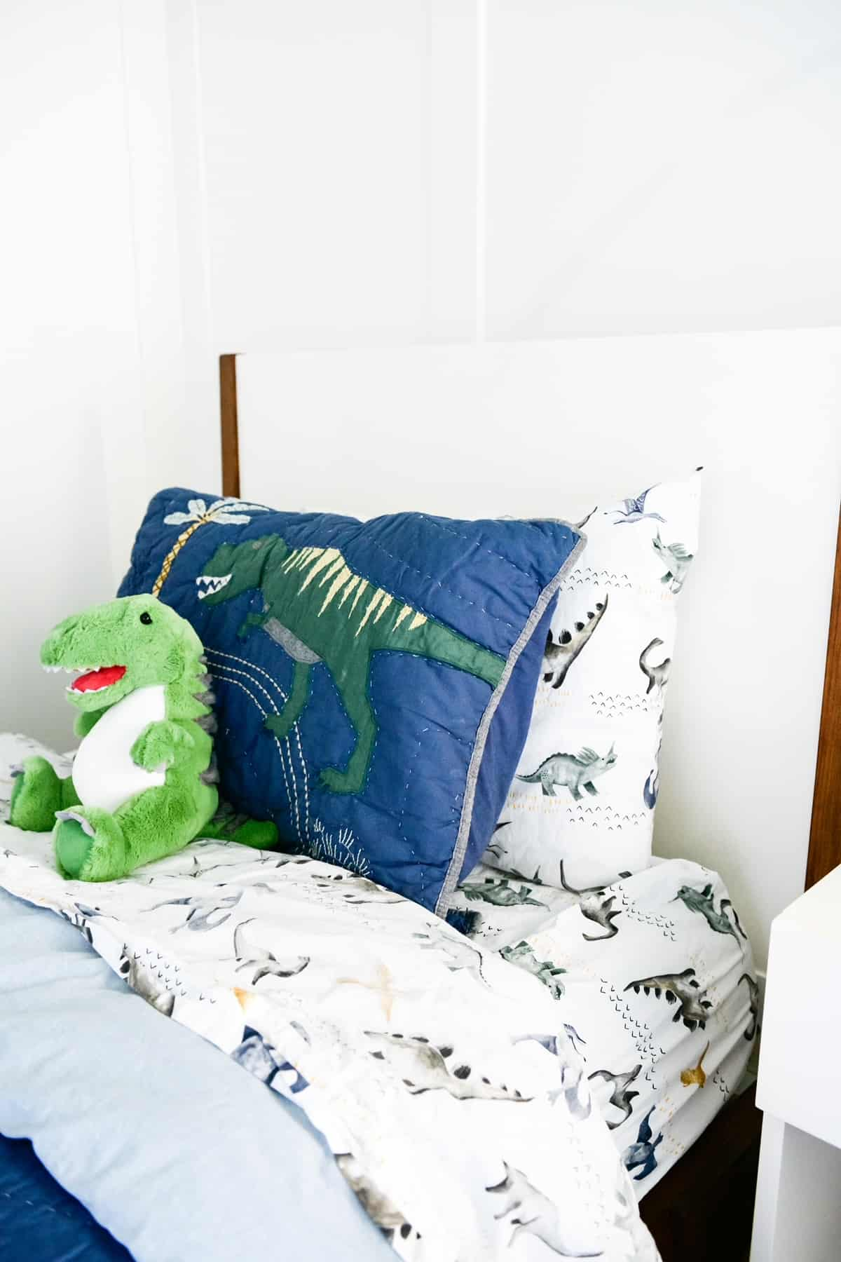 Dinosaur Themed Room by popular Dallas life and style blog, Glamorous Versatility: image of a boys room with a green painted ceiling, dinosaur bedding, framed dinosaur artwork, dinosaur lamp, board and batten walls, and a white night stand.