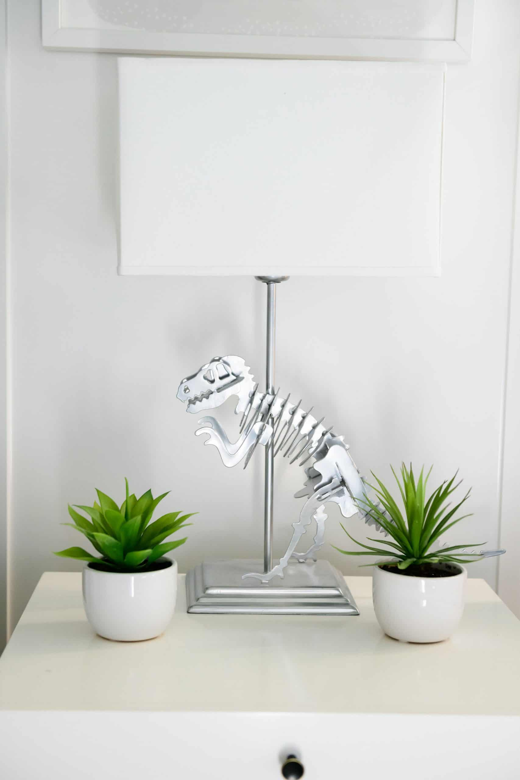 Dinosaur Themed Room by popular Dallas life and style blog, Glamorous Versatility: image of a boys room with a dinosaur lamp, board and batten walls, and a white night stand.