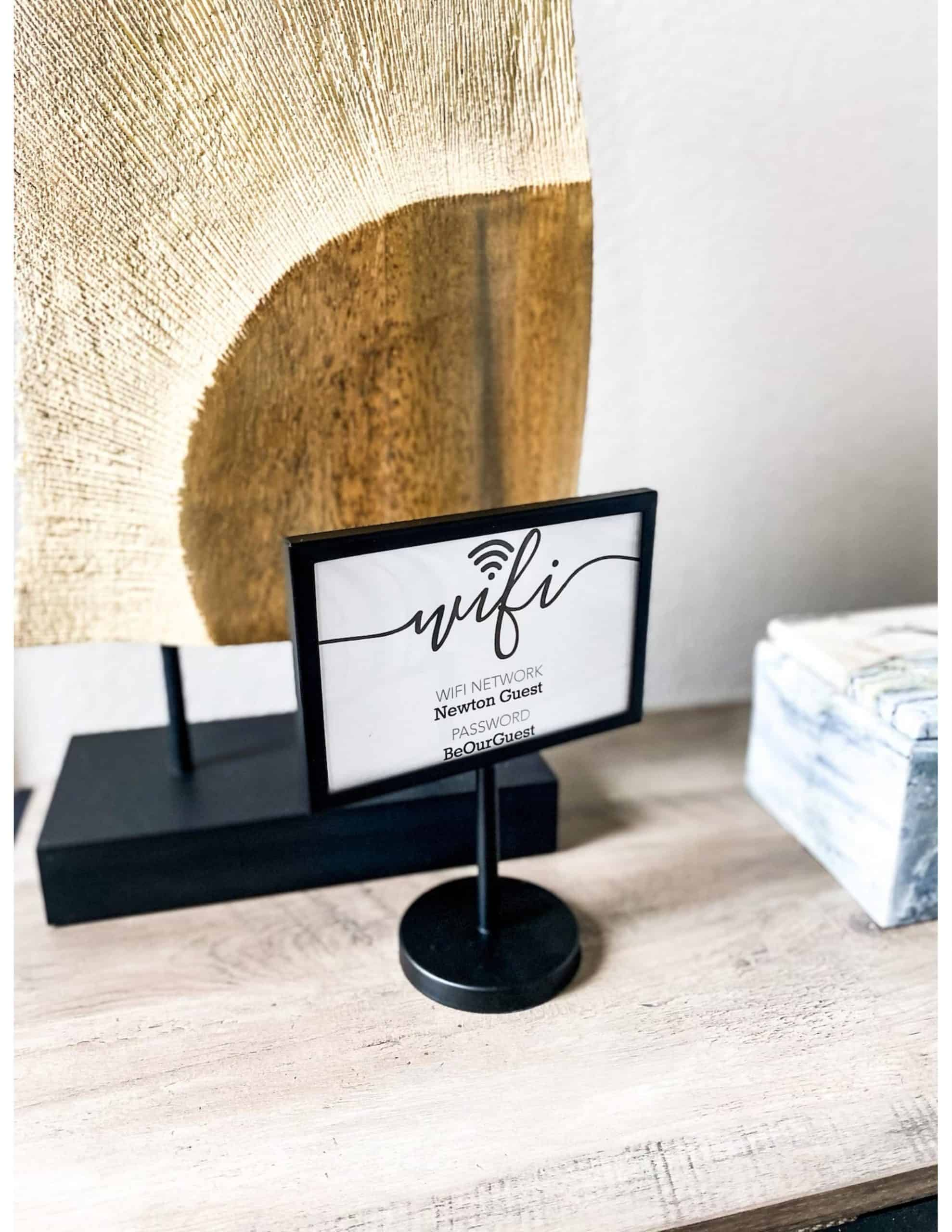 Modern Guest Bedroom by popular Dallas life and style blog, Glamorous Versatility: image of a wifi information card on a light woo table in front of a rock art piece.
