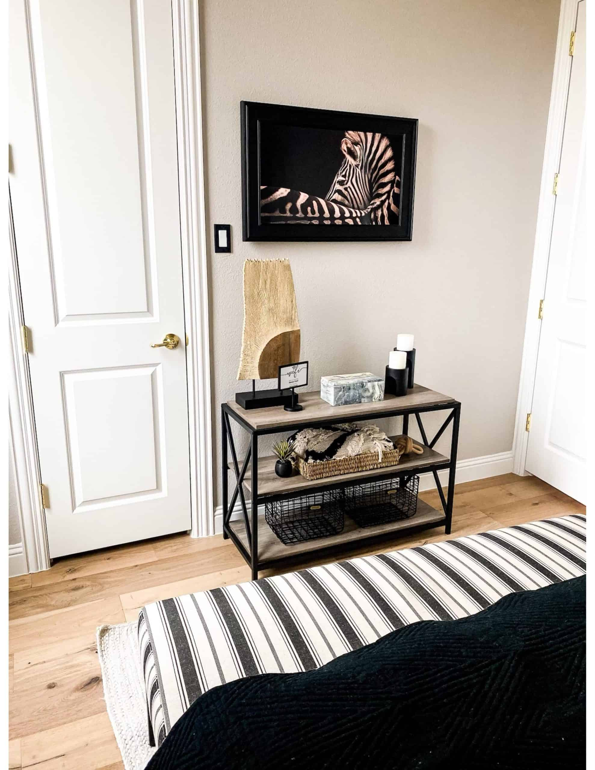 Modern Guest Bedroom by popular Dallas life and style blog, Glamorous Versatility: image of a guest bedroom decorated with framed zebra photo, black and white stripe bench, and rustic wood and metal table decorated with candles, sea grass basket, and black metal baskets.