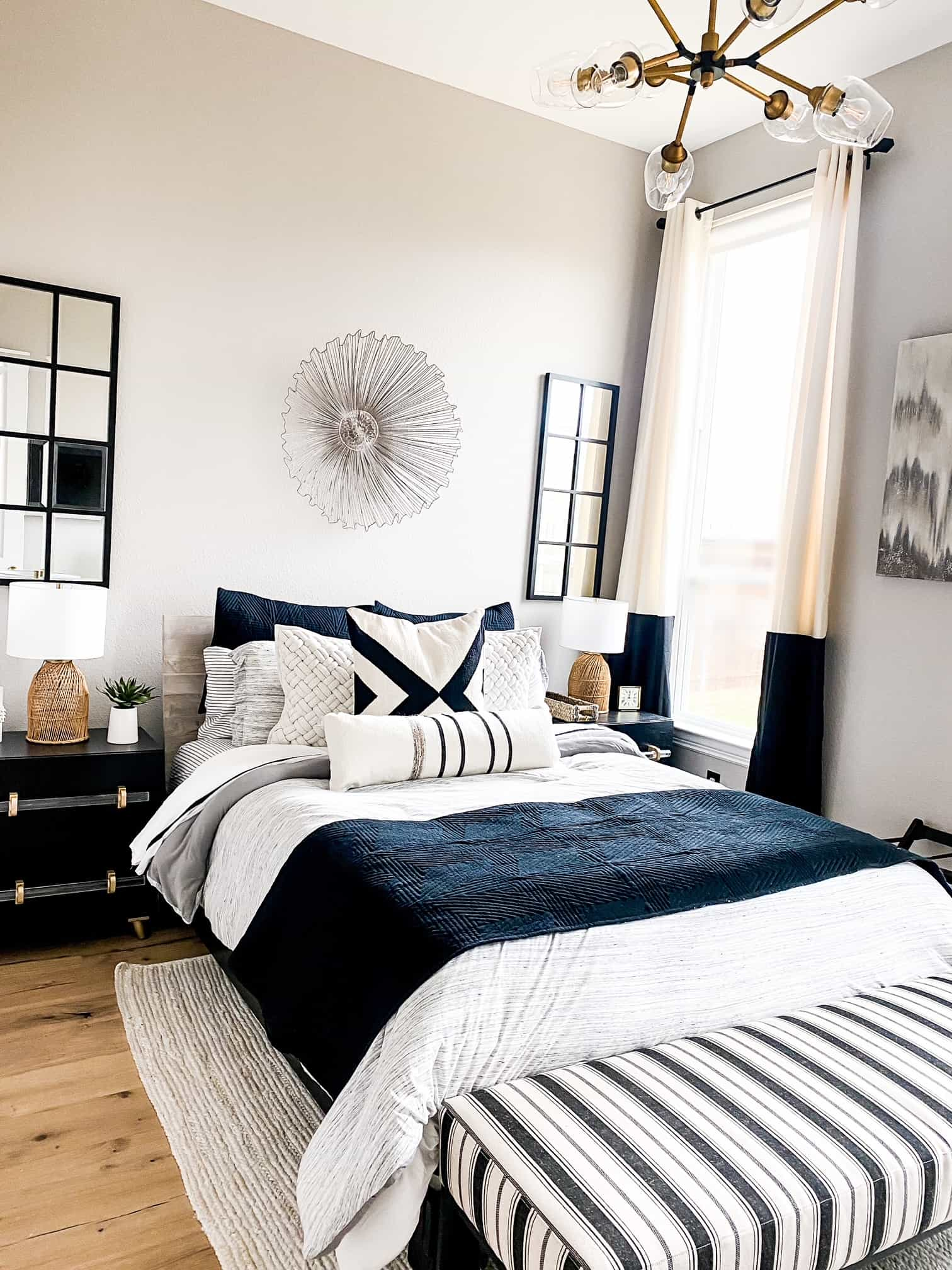 Modern Guest Bedroom by popular Dallas life and style blog, Glamorous Versatility: image of a guest bedroom decorated with black dressers, black and white striped bench, queen size bed with black white, and blue bedding, black and white drapes, modern brass and glass light fixture, woven cream area rug, wicker lamps, and black frame mirrors.