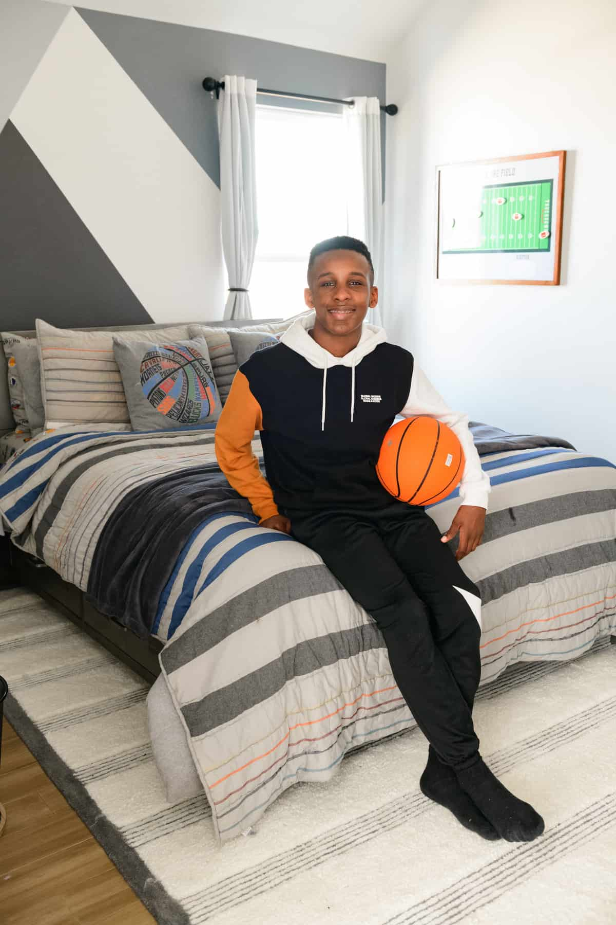 Teenage Boy Bedroom by popular Dallas life and style blog, Glamorous Versatility: image of a teenage boy holding a basketball and sitting on a bed with a blue, white, and grey strip bed cover.
