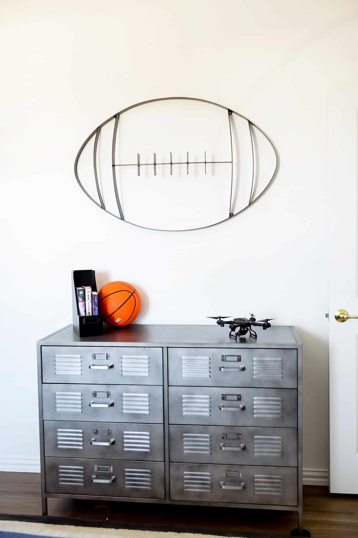 Teenage Boy Bedroom by popular Dallas life and style blog, Glamorous Versatility: image of a metal football wall decal hanging over a grey metal locker style dressers.