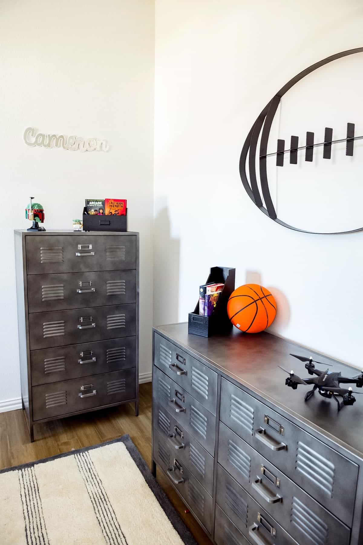 Teenage Boy Bedroom by popular Dallas life and style blog, Glamorous Versatility: image of grey metal locker style dressers and a metal football wall decal.