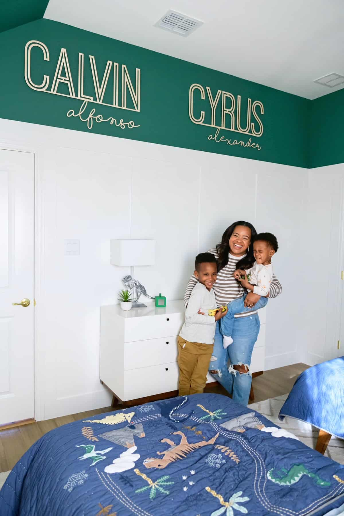 Bedroom Paint Colors by popular Dallas life and style blog, Glamorous Versatility: image of a mom and her two boys standing together in a room decorated with a white dresser, dinosaur bedding, and wall name decals.