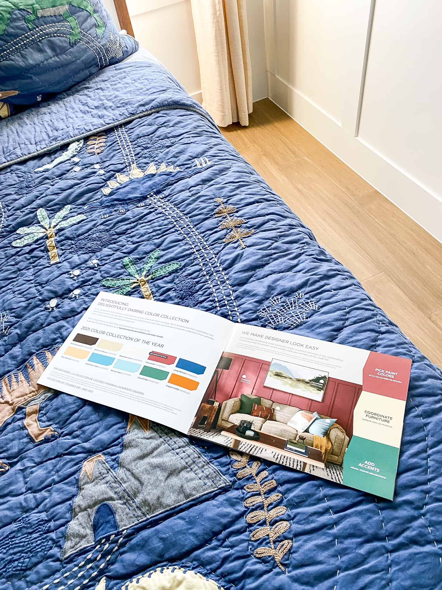 Bedroom Paint Colors by popular Dallas life and style blog, Glamorous Versatility: image of a paint catalogue on a bed with dinosaur bedding.
