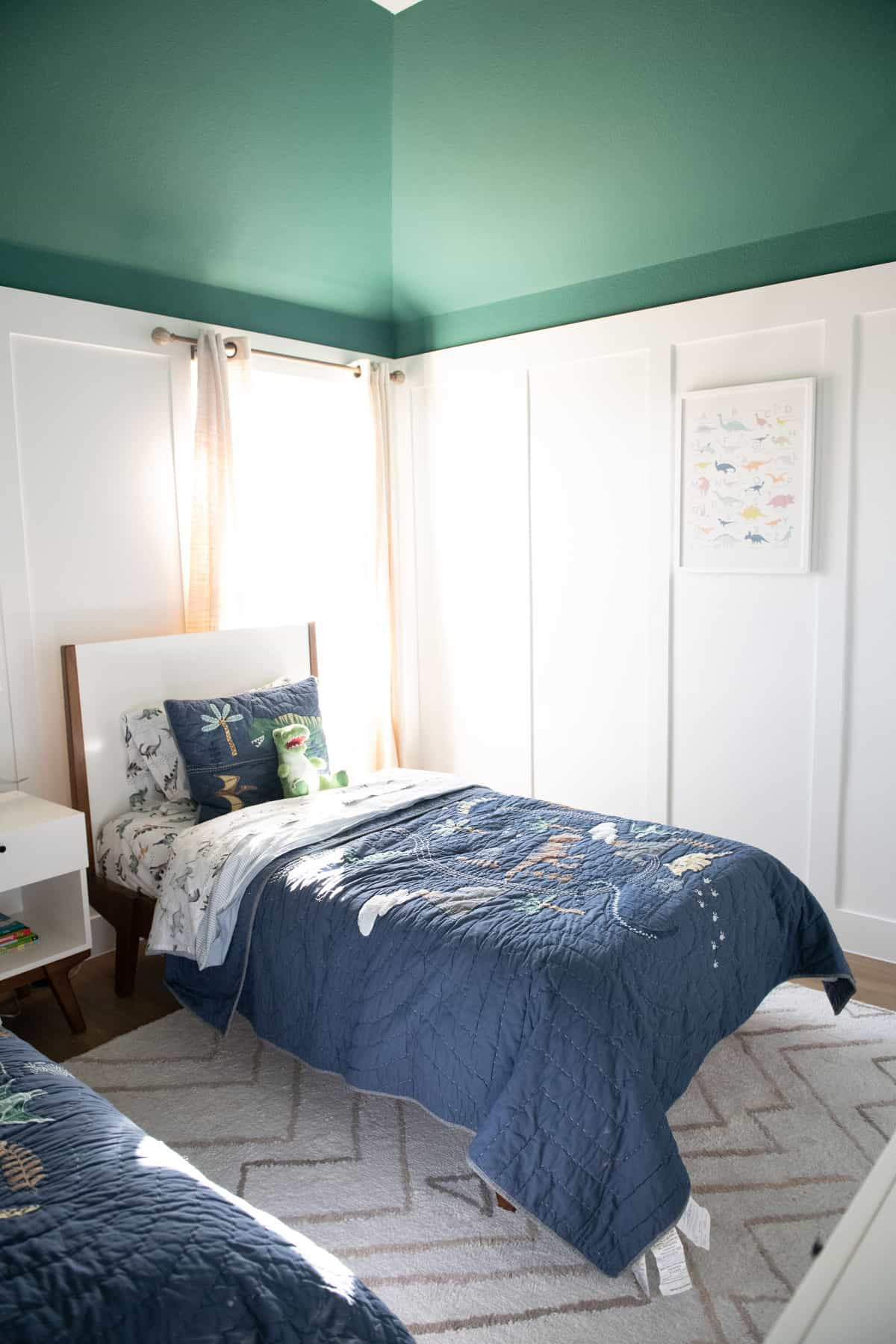 Bedroom Paint Colors by popular Dallas life and style blog, Glamorous Versatility: image of a boys' bedroom decorated with with twin beds, white headboards, dinosaur bedding, framed dinosaur art, and a white night stand with a lamp and faux plants resting on it.
